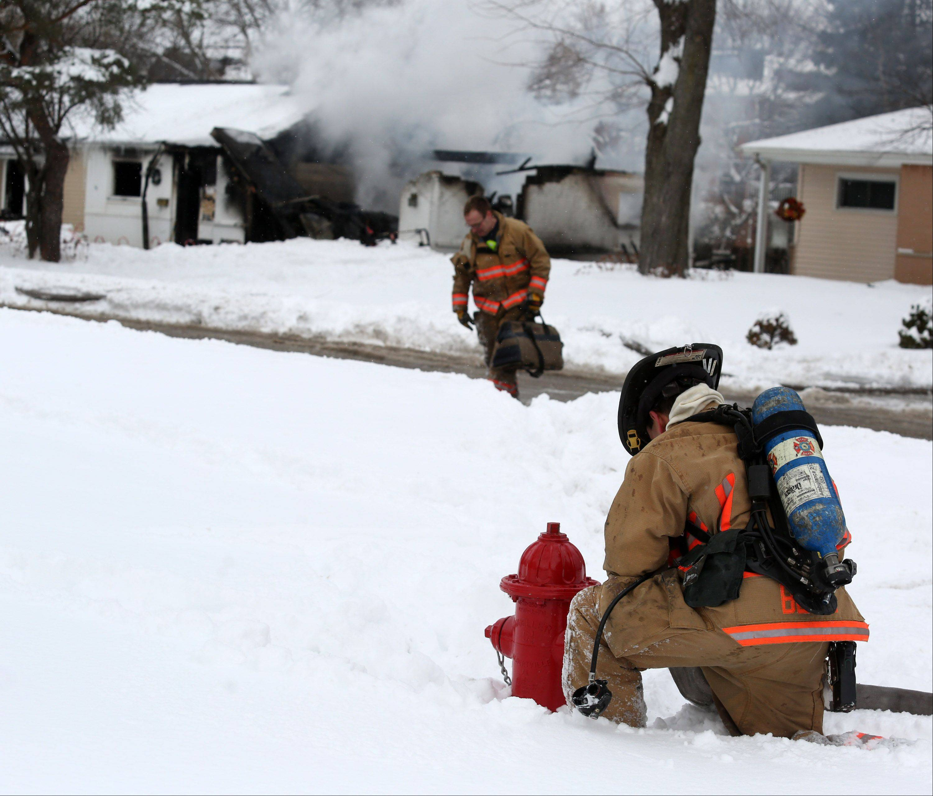 A Hoffman Estates firefighter connects a hose to a fire hydrant near a house fire on Basswood Street on Wednesday. Two pets were later found dead, and the home was left completely uninhabitable.