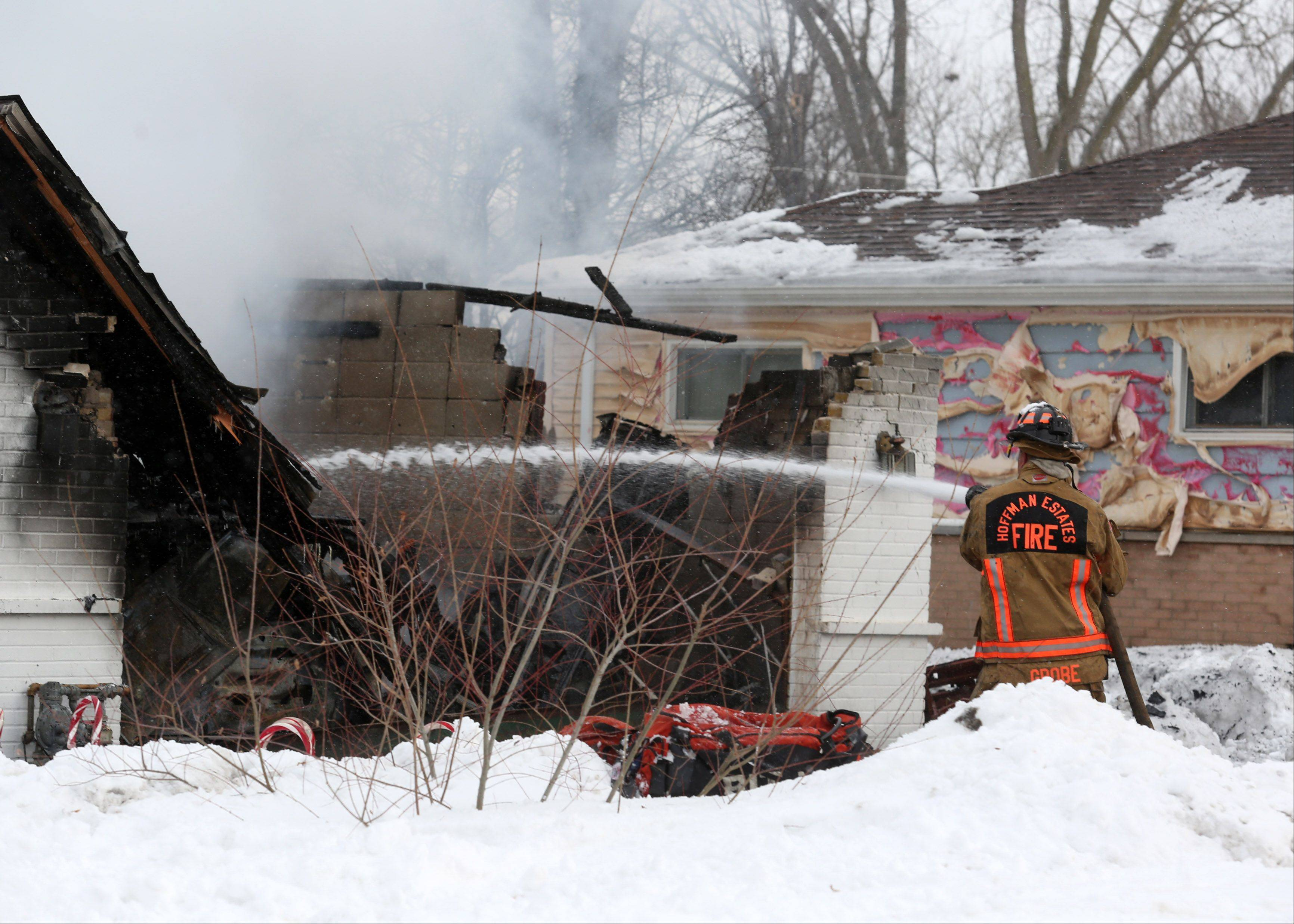 A Hoffman Estates firefighter sprays water on a house fire Wednesday afternoon on Basswood Street. Fire investigators are searching for the cause of the fire, which left the home uninhabitable.