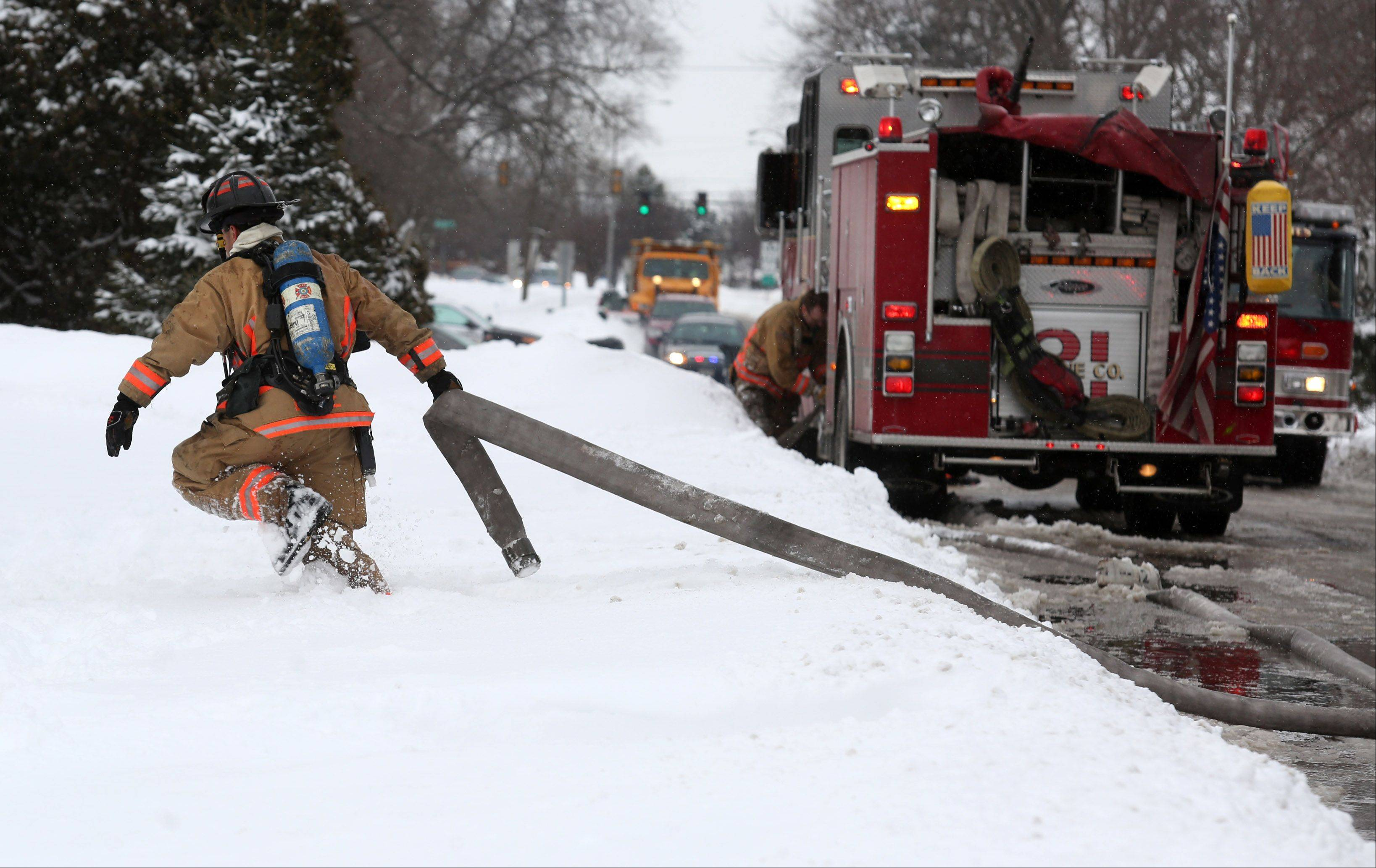 A Hoffman Estates firefighter pulls a hose to a fire hydrant near a house fire Wednesday afternoon on Basswood Street. Two pets were later found dead, and the home was left completely uninhabitable.