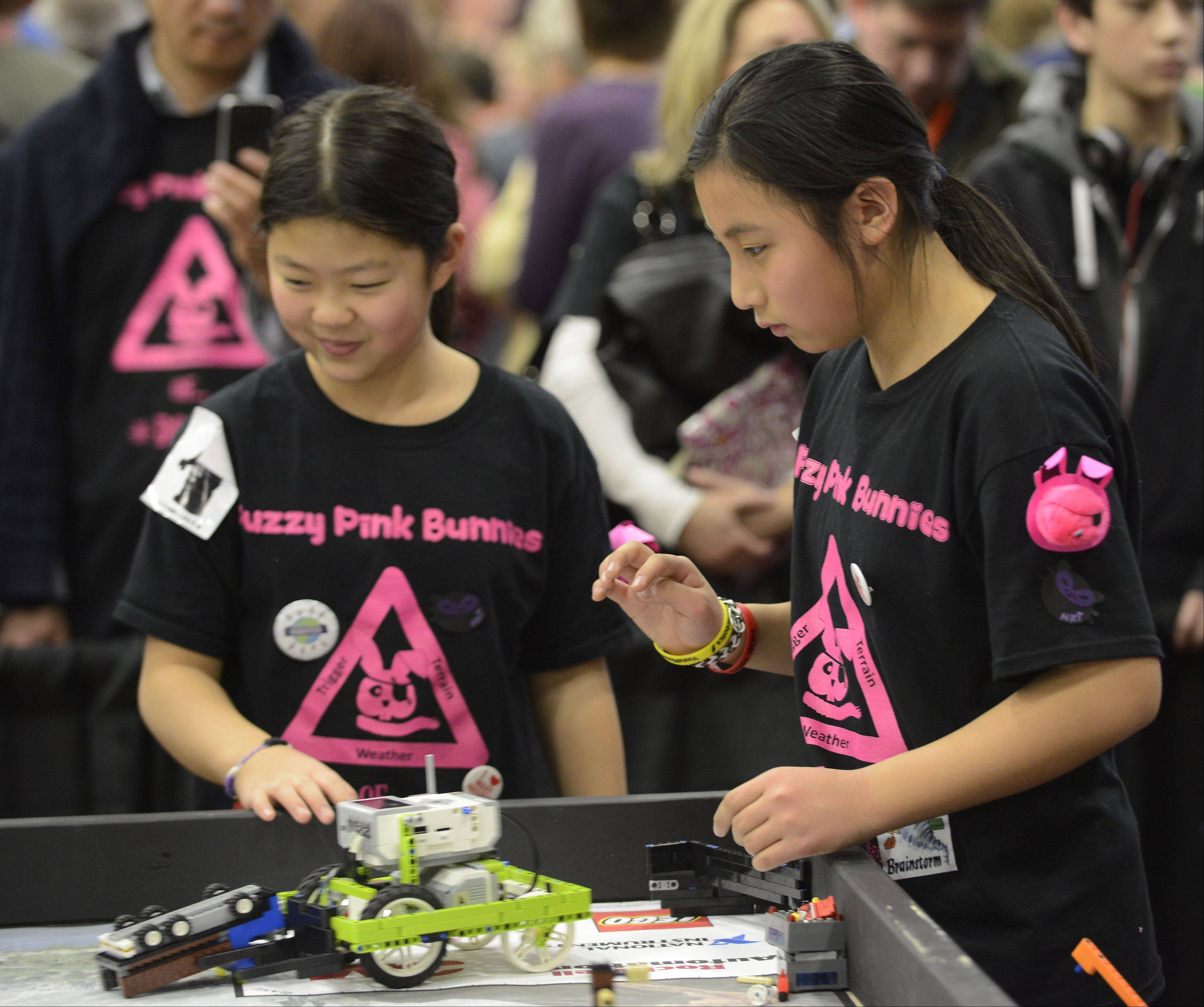 "Sixth-graders Jane Pak, left, and Kaitlyn Lu of the ""Fuzzy Pink Bunnies of Doom"" team from Woodlawn Middle School in Long Grove compete Saturday for the Illinois First Lego League's Northern Illinois title at the Forest View Educational Center in Arlington Heights."