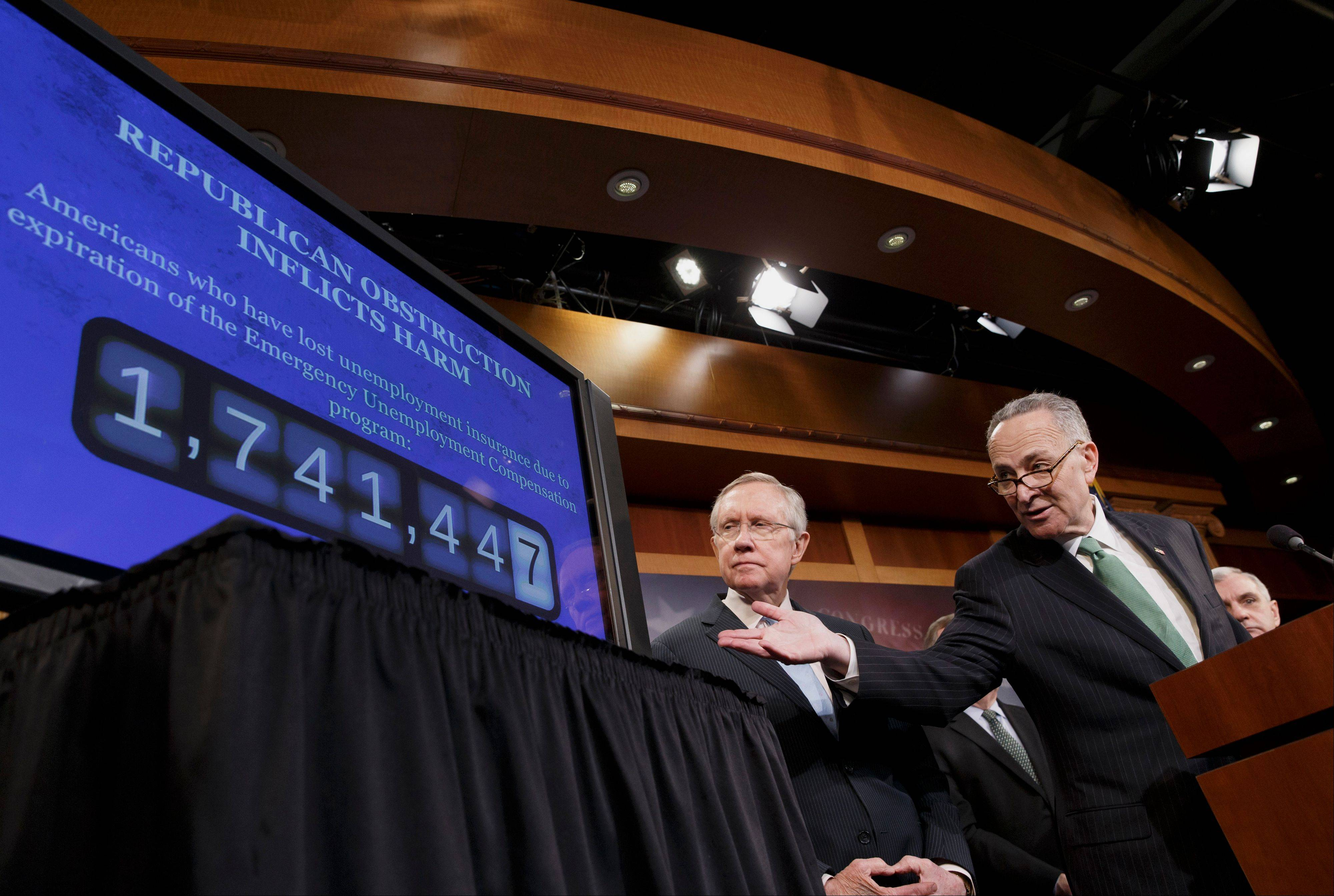 Sen. Charles Schumer, the Democratic Policy Committee chairman, right, accompanied by Senate Majority Leader Harry Reid, points to a graphic during a news conference on Capitol Hill Thursday, where they charged Republicans are thwarting Democratic efforts pass a bill to extend unemployment benefits which expired at the end of last year.
