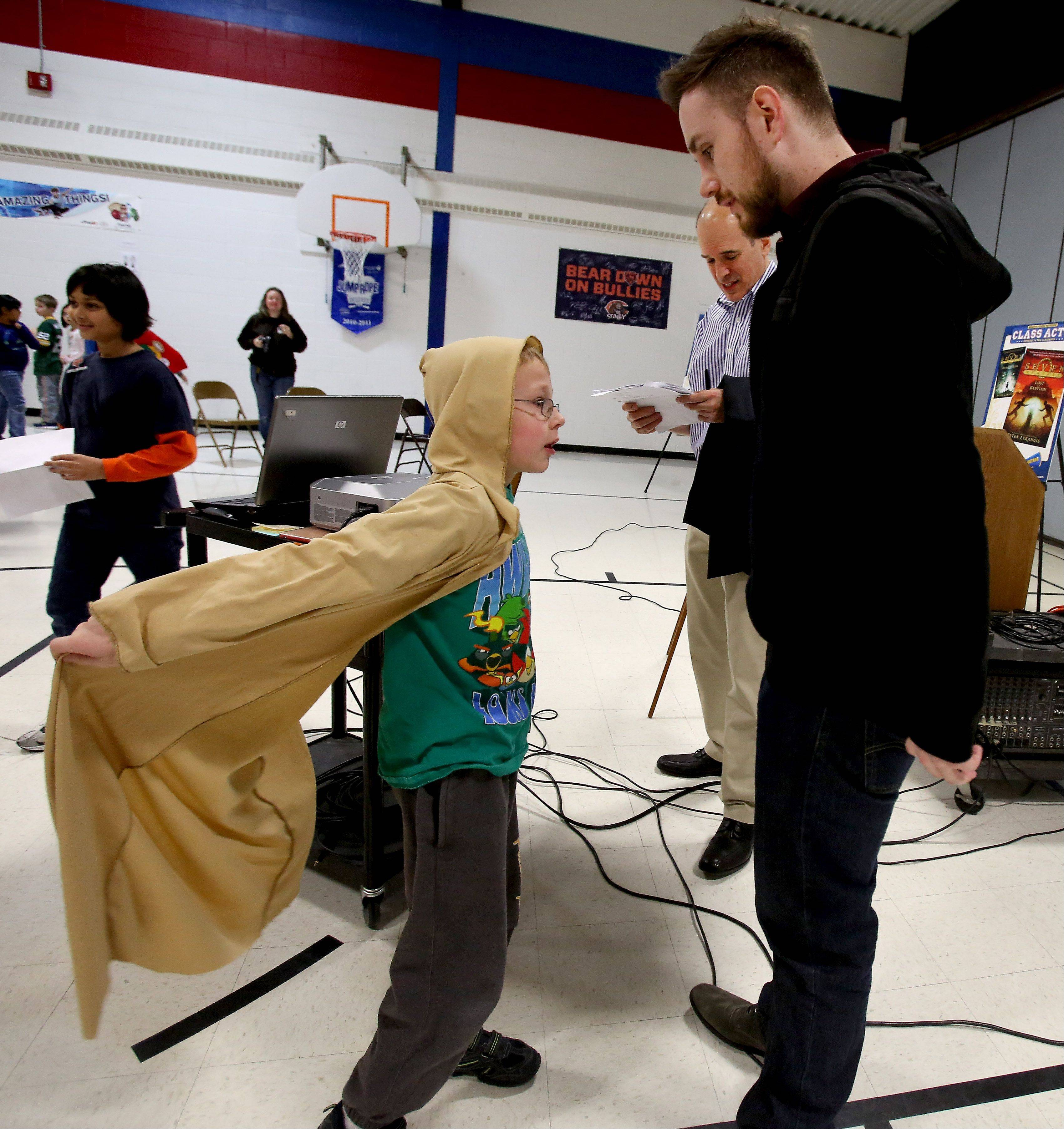 "Fifth-grader Noah Ranson, sporting a snazzy cape, has a word with author Jeramey Kraatz, author of the ""Cloak Society"" series, after a Naperville READS presentation Thursday at Longwood Elementary School."