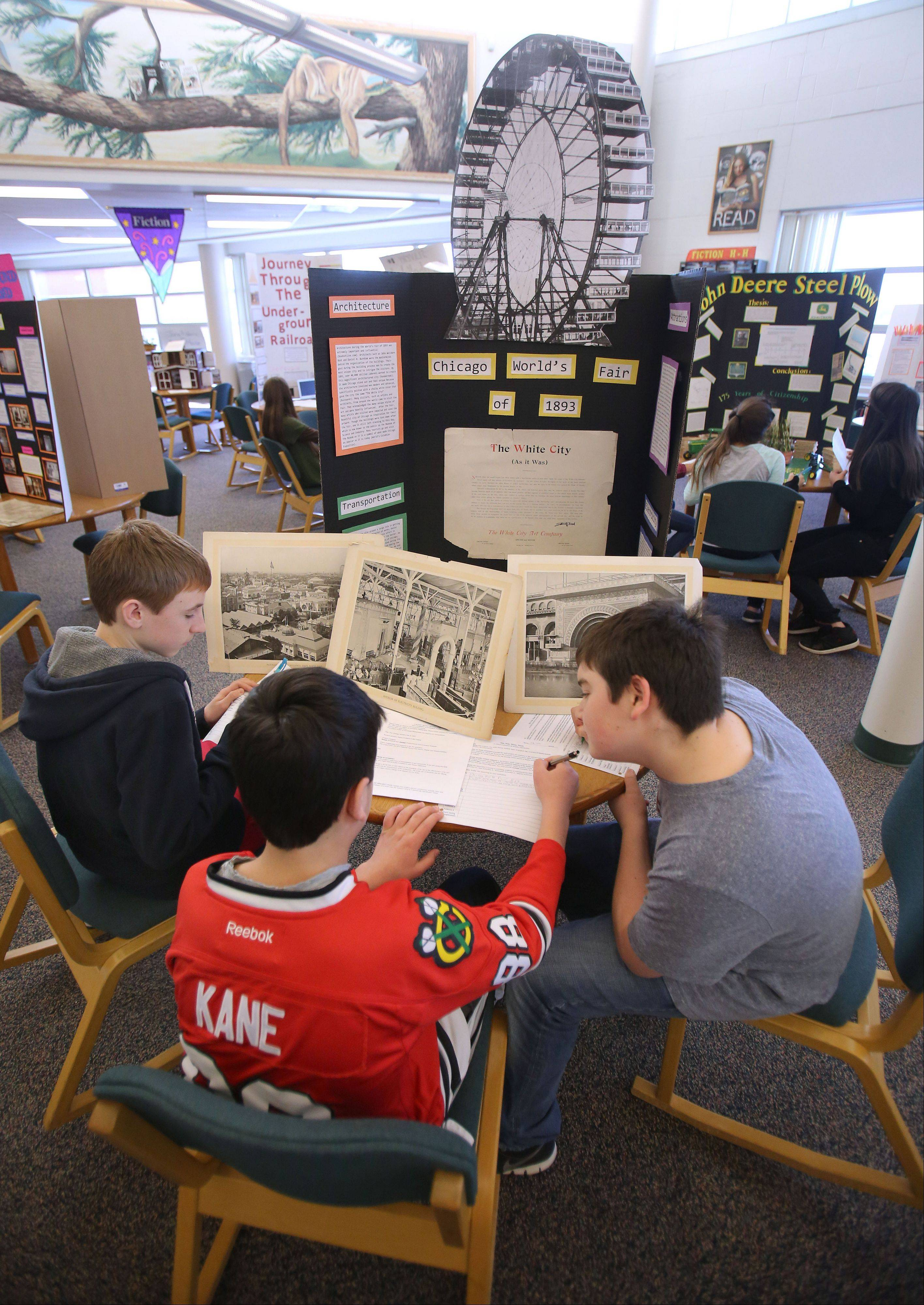Freshman Tom Zayats, left, Jacob Gordon and Ryan Ginsberg study a display covering the Chicago World's Fair during a history fair in the Vernon Hills High School library Thursday. The fair featured traditional cardboard displays, as well as websites and video documentaries.