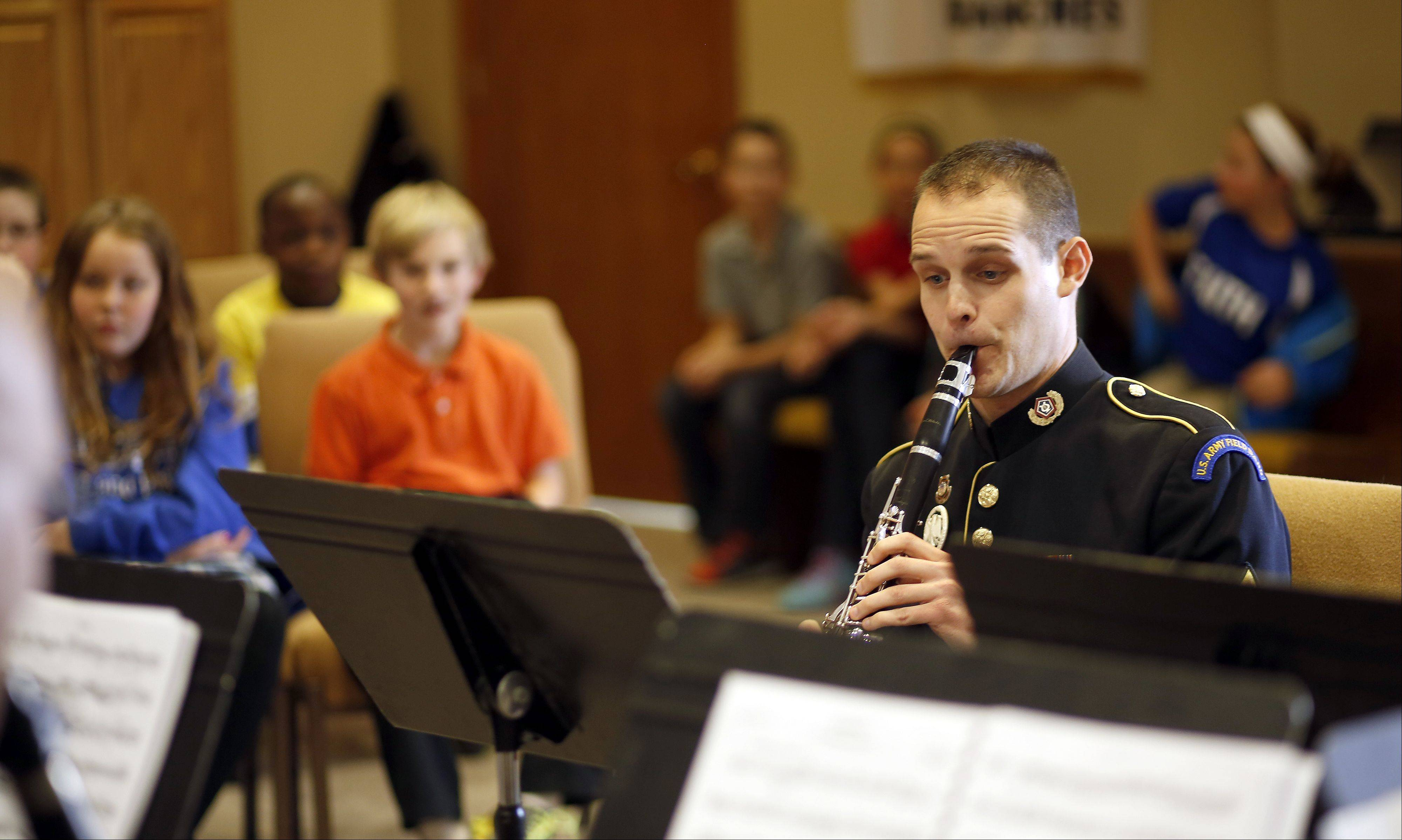 Faith Christian Academy alumnus Joel Klenke performs Thursday for third- and fourth-grade students in Geneva. Klenke and his brother, Jeremy, and members of the U.S. Army Field Band conducted a mini concert for students.
