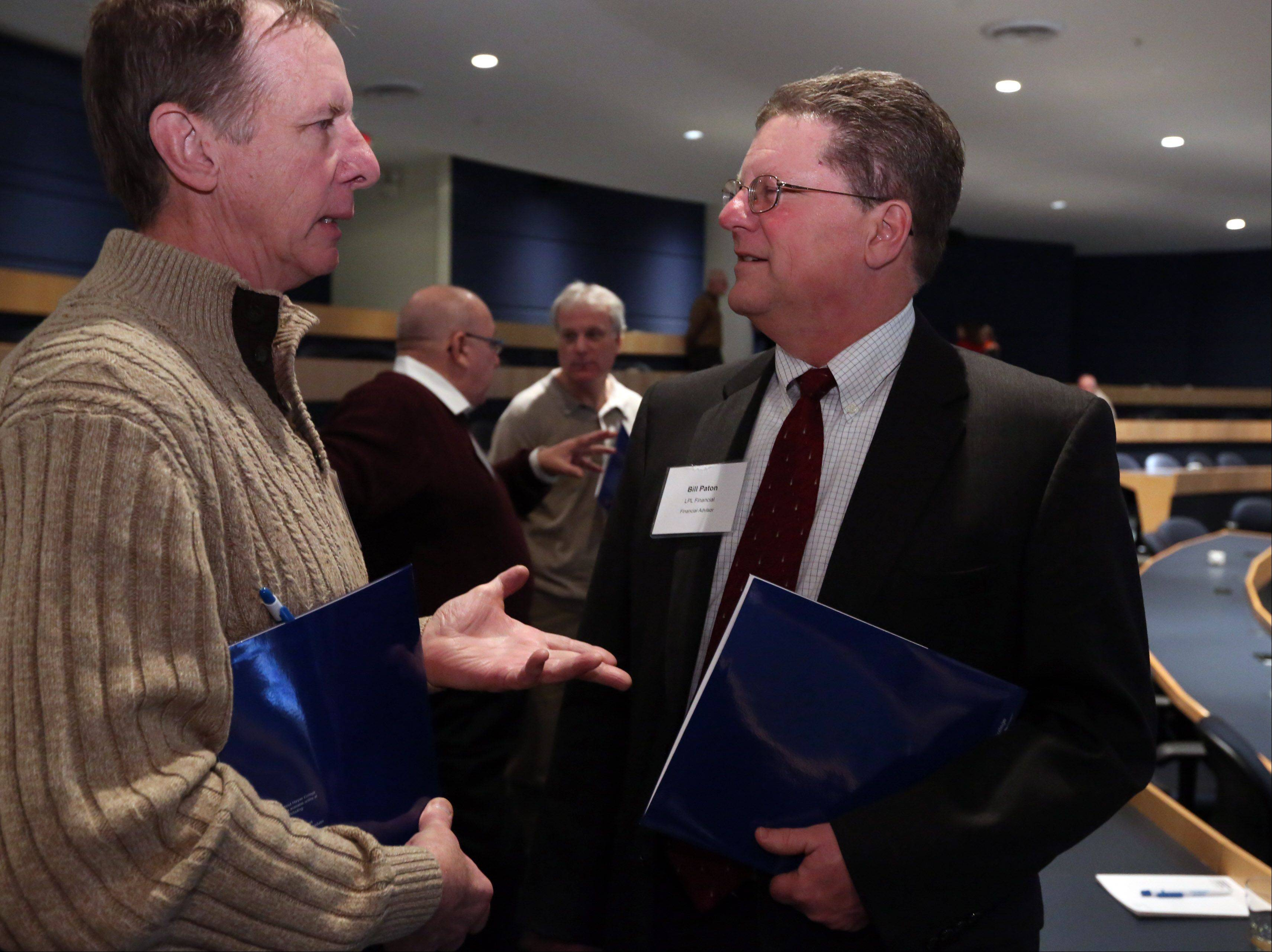 James Nielsen, owner of Handyman Jim, left, speaks with Bill Paton, financial advisor for LPL Financial, after an economic outlook breakfast at the Wojcik Conference Center at Harper College on Thursday in Palatine.