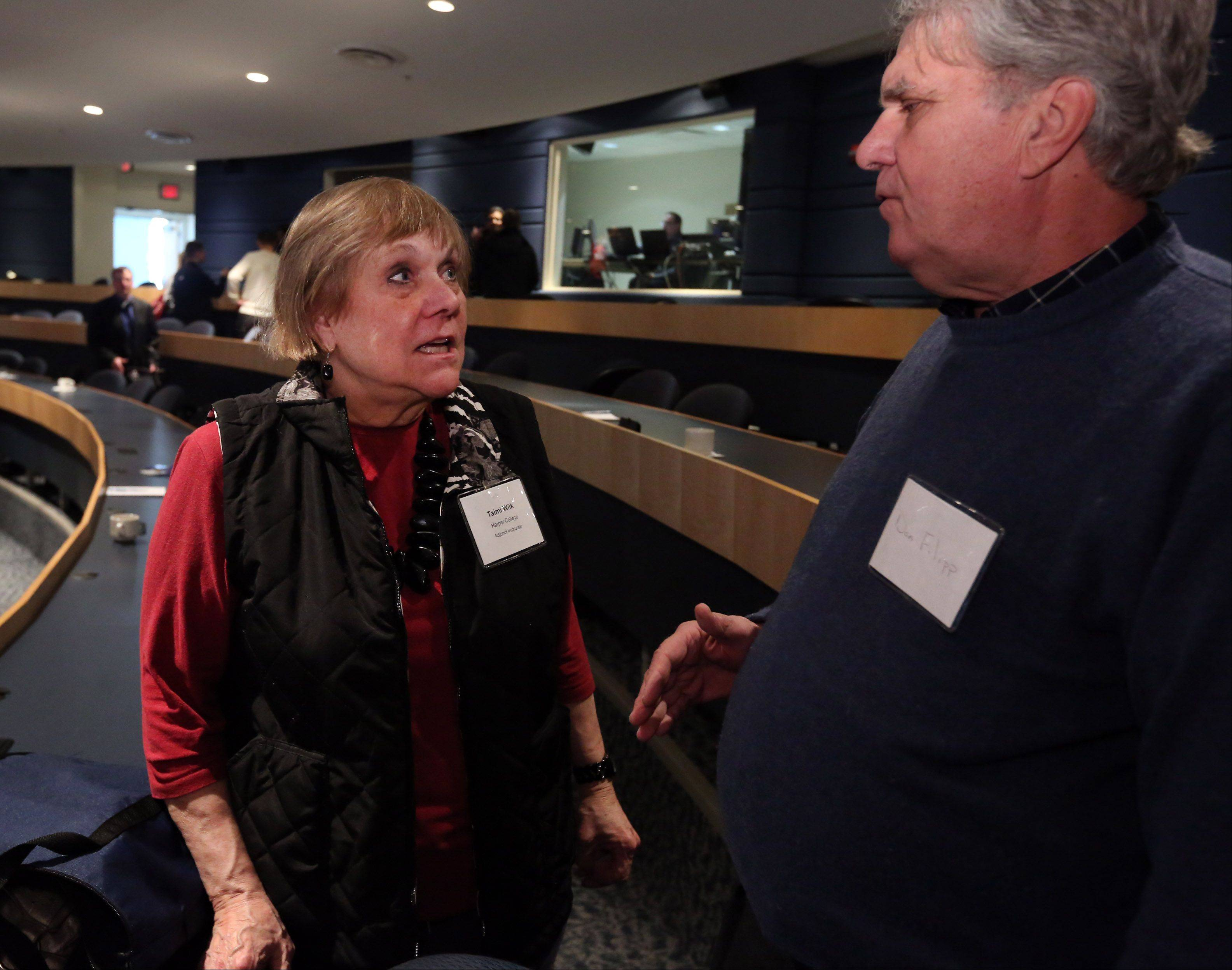 Taimi Wilk, Harper College adjunct instructor, left, talks with Don Filipp of Barrington, after an economic outlook breakfast at the Wojcik Conference Center at Harper College on Thursday in Palatine.