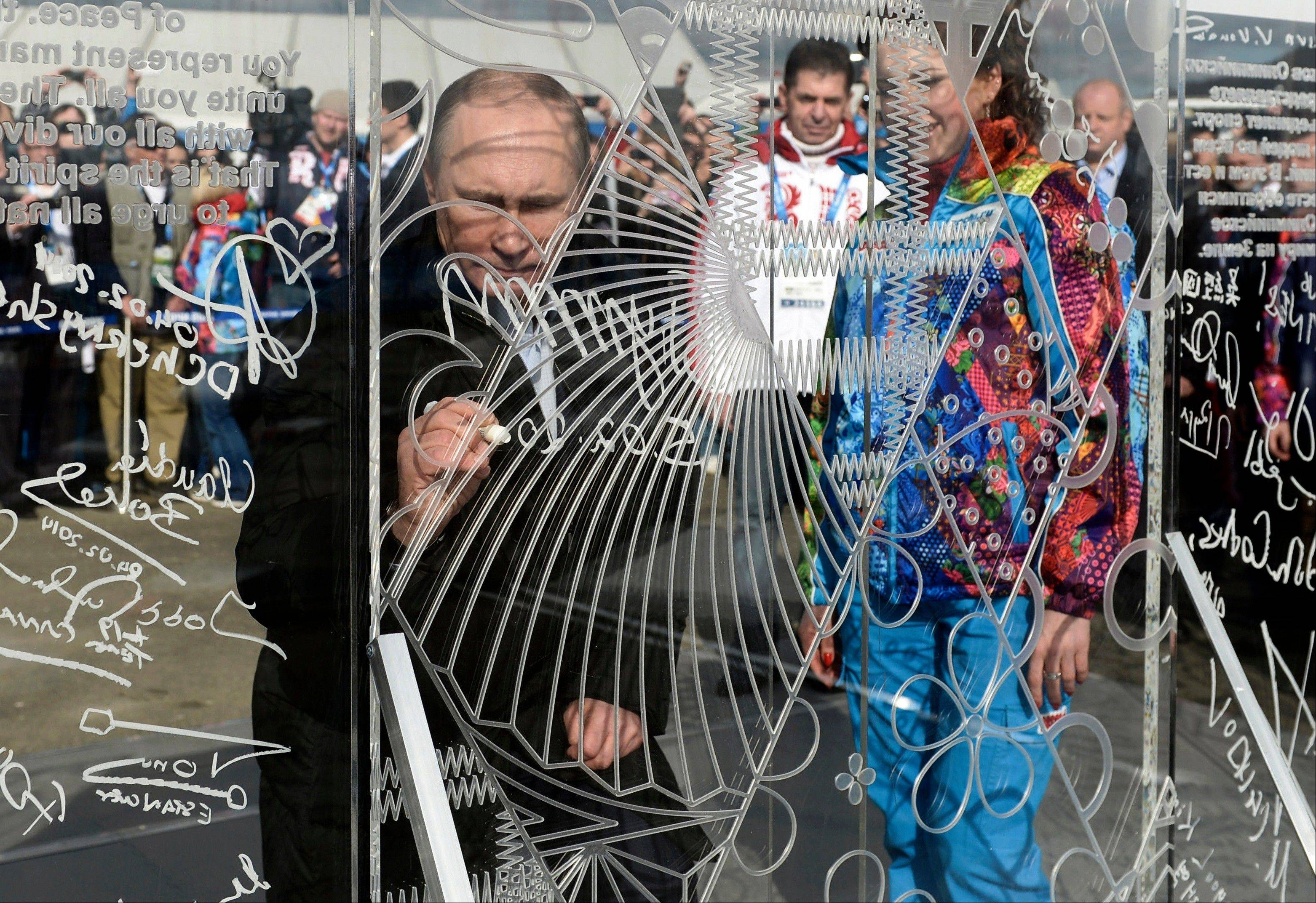 Russian President Vladimir Putin signs a wall while visiting the Coastal Cluster Olympic Village ahead of the Sochi 2014 Winter Olympics on Wednesday in Sochi, Russia.