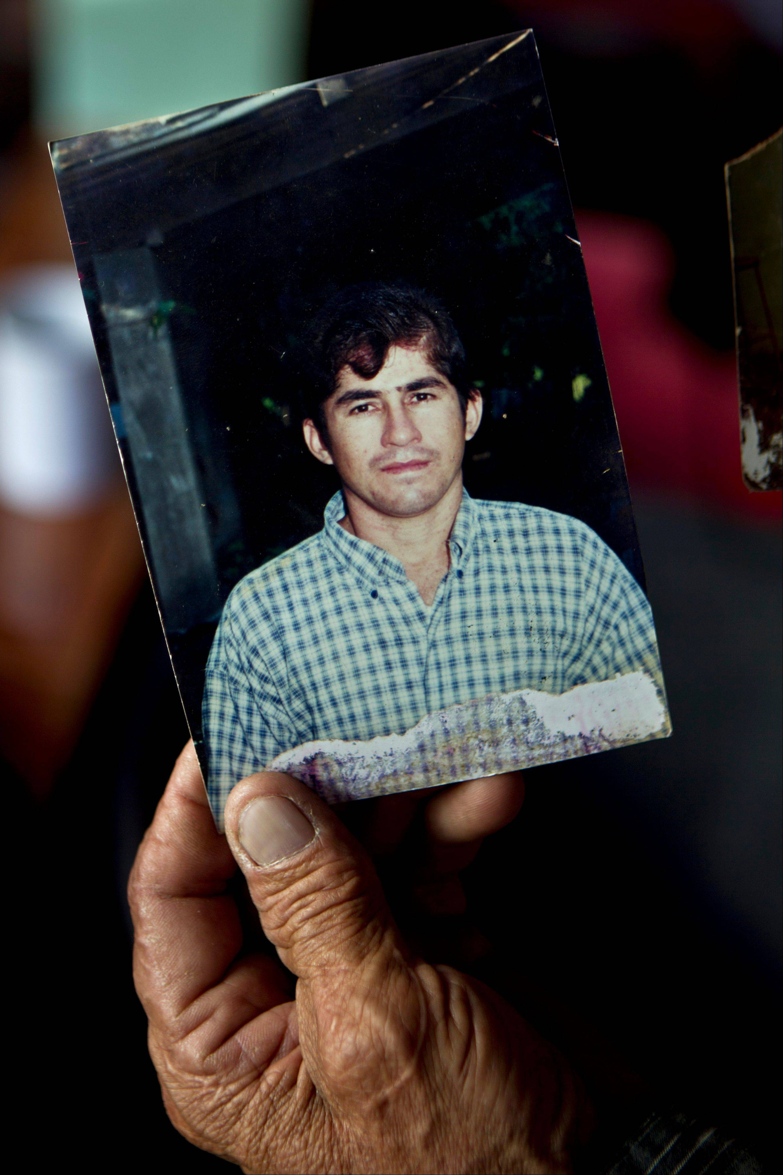Jose Ricardo Orellana shows a photo of his son Jose Salvador Alvarenga when he was in his late twenties during an interview at his home in the village of Garita Palmera, El Salvador, Tuesday. The account of Alvarenga's survival after more than 13 months in an open boat has proven a double miracle for his family, who lost touch with him years ago and thought he was dead. Alvarenga says he left Mexico in December 2012 for a day of shark fishing and ended up on the remote Marshall Islands.