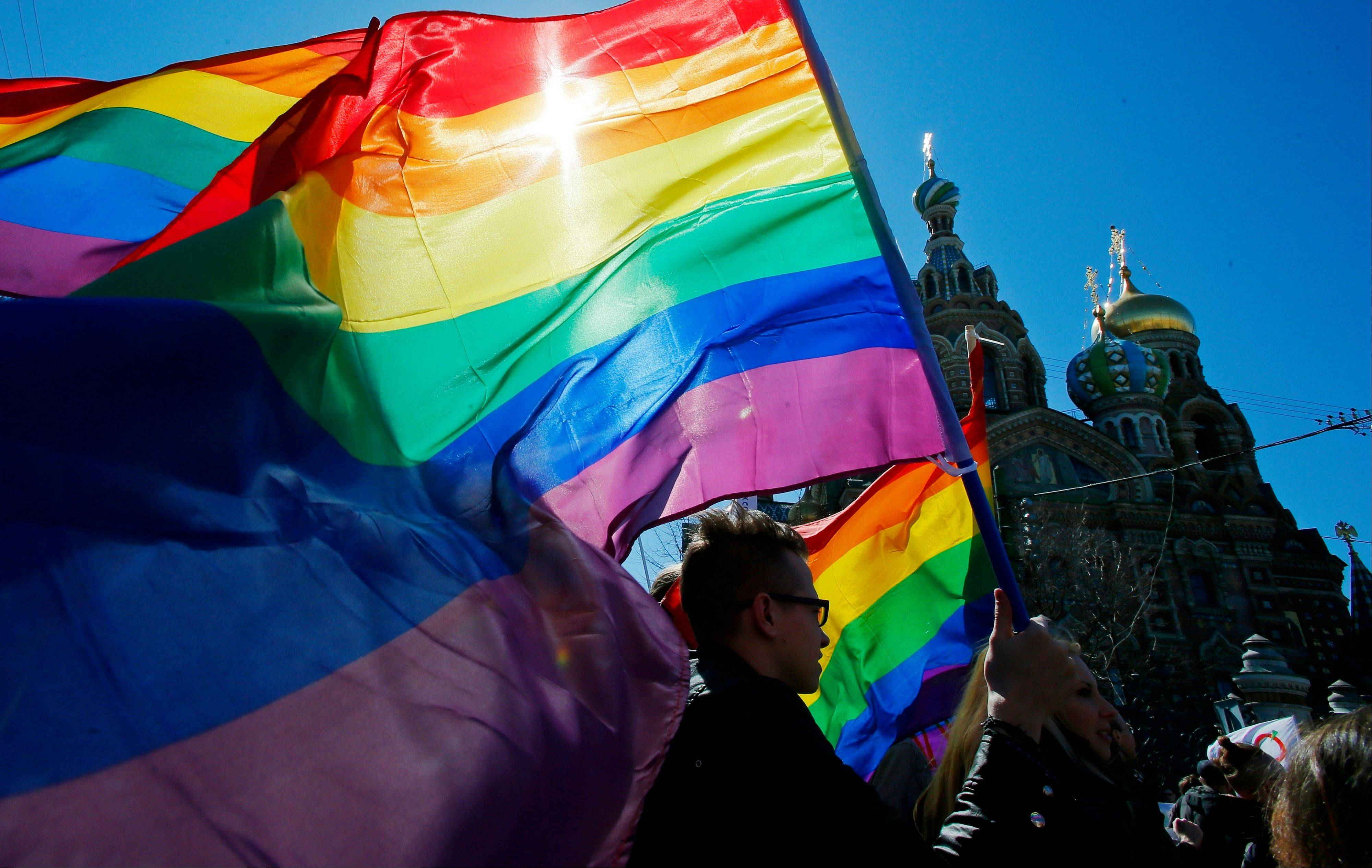 "Gay rights activists carry rainbow flags as they march during a May Day rally in St. Petersburg, Russia, last May. When the Sochi Winter Olympics begin Friday, Feb. 7, many will be watching to see whether Russia will enforce its law banning gay ""propaganda"" among minors if athletes, fans or activists wave rainbow flags or speak out in protest. The message so far has been confusing."