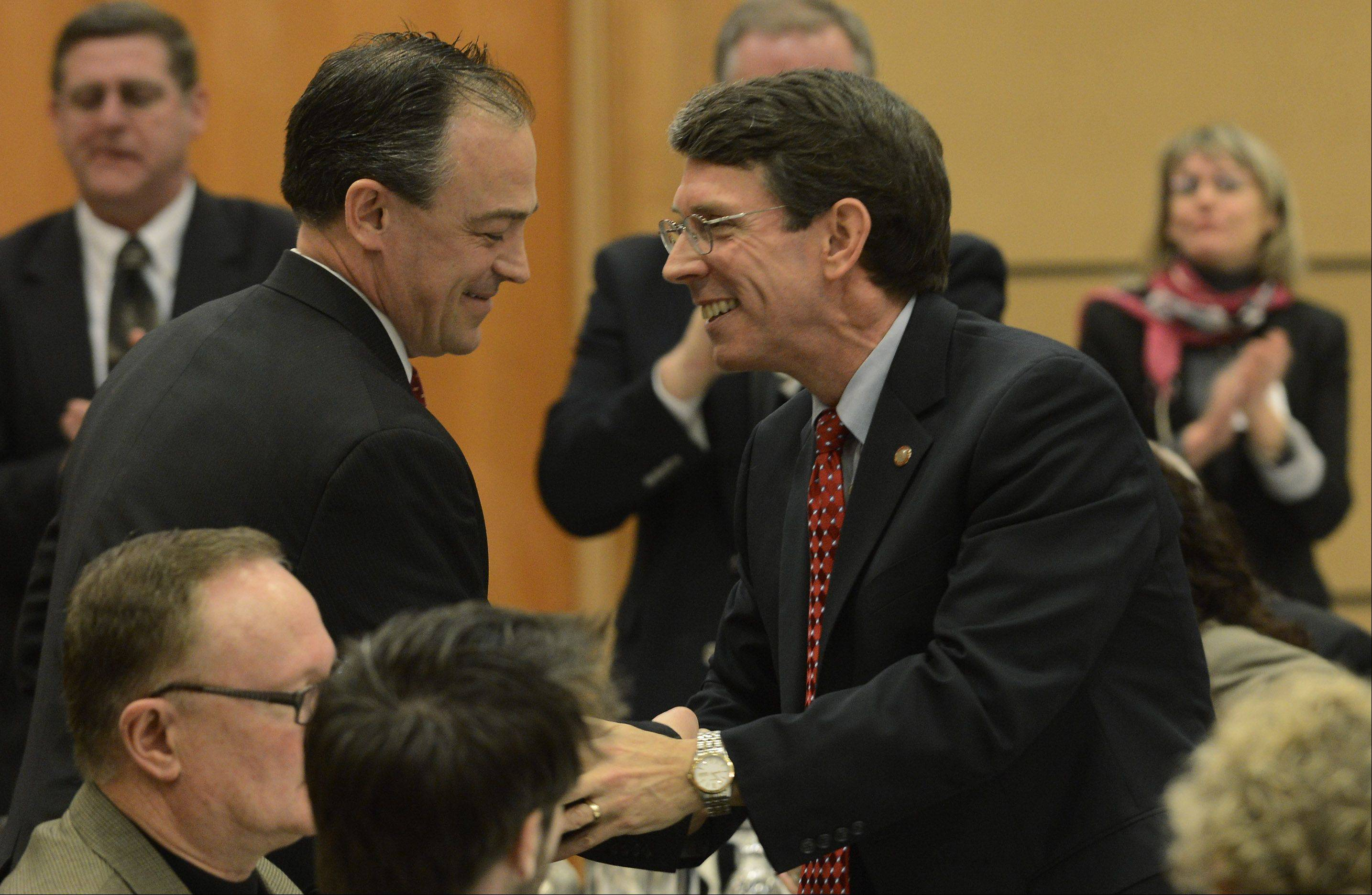 Arlington Heights Mayor Tom Hayes, right, shakes hands with Will Beiersdorf following his speech at the community prayer breakfast in Arlington Heights Thursday.