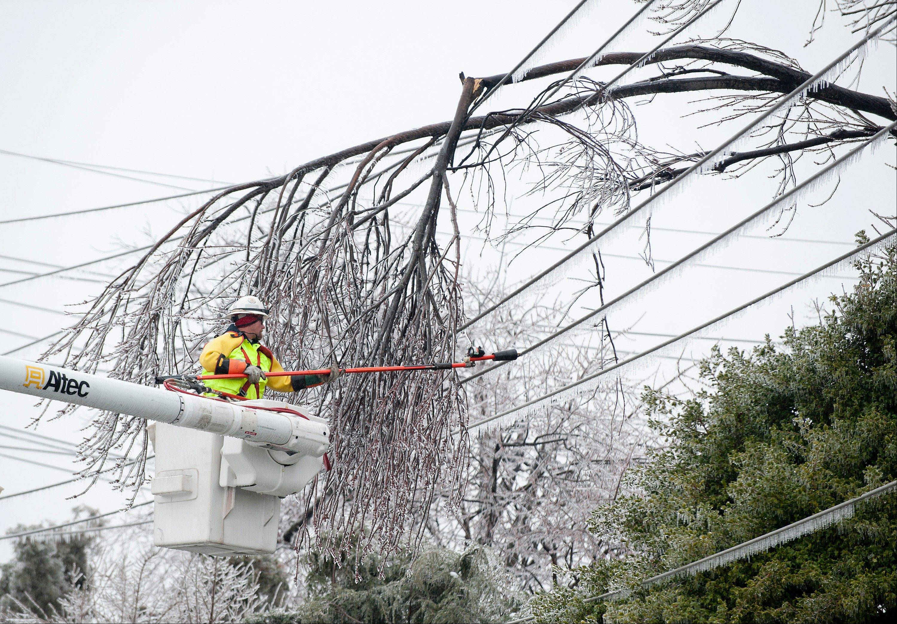 A Potomac Edison worker begins to remove a number of fallen branches from a high voltage line in Frederick, Md. Many area homes and traffic lights were without power.