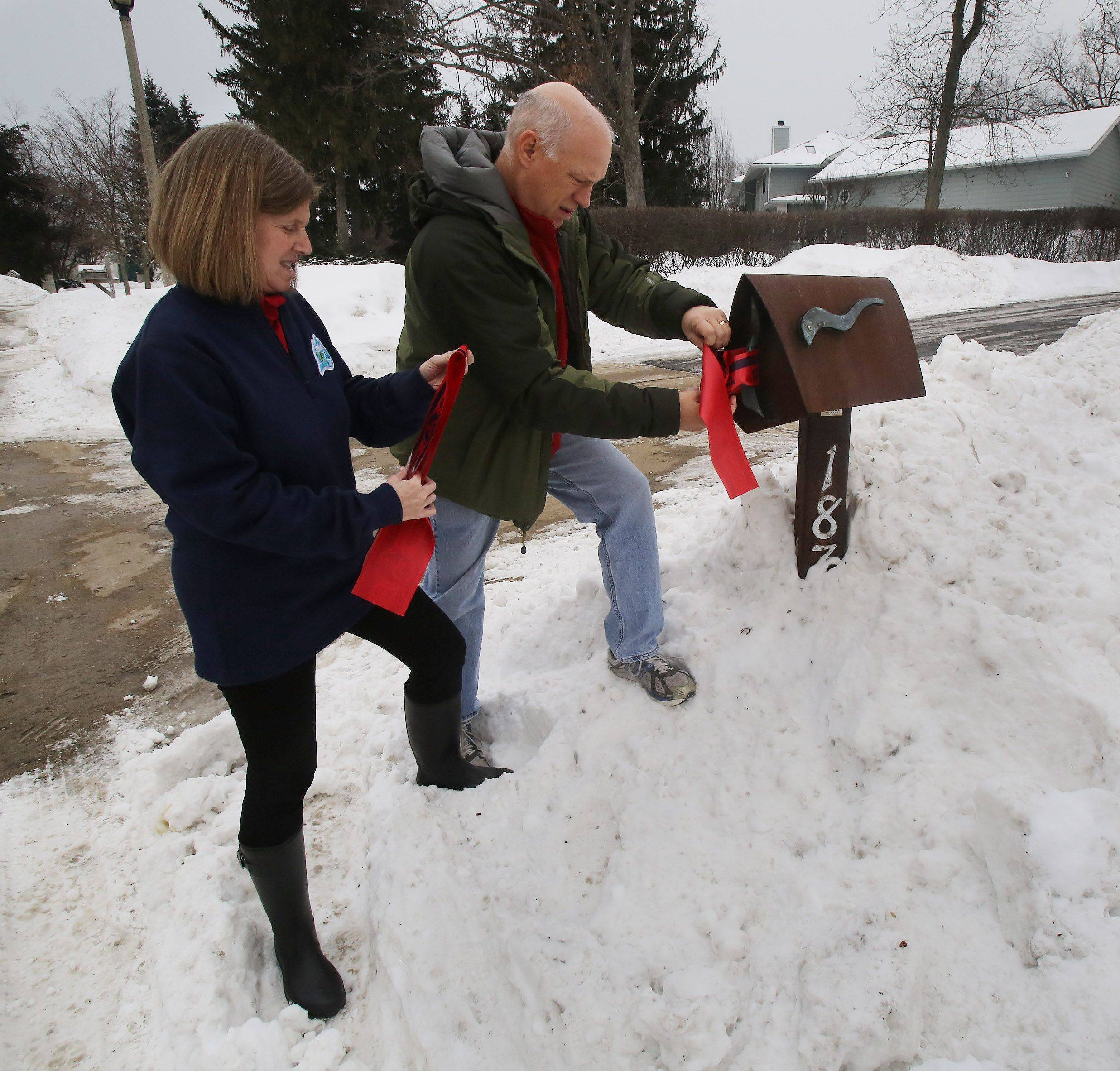 Steve and Marla Brown of Highland Park tie a ribbon to their mailbox before leaving for the Sochi Olympics to watch their son Jason compete in men's figure skating. Highland Park has handed out ribbons to display in support of Jason.