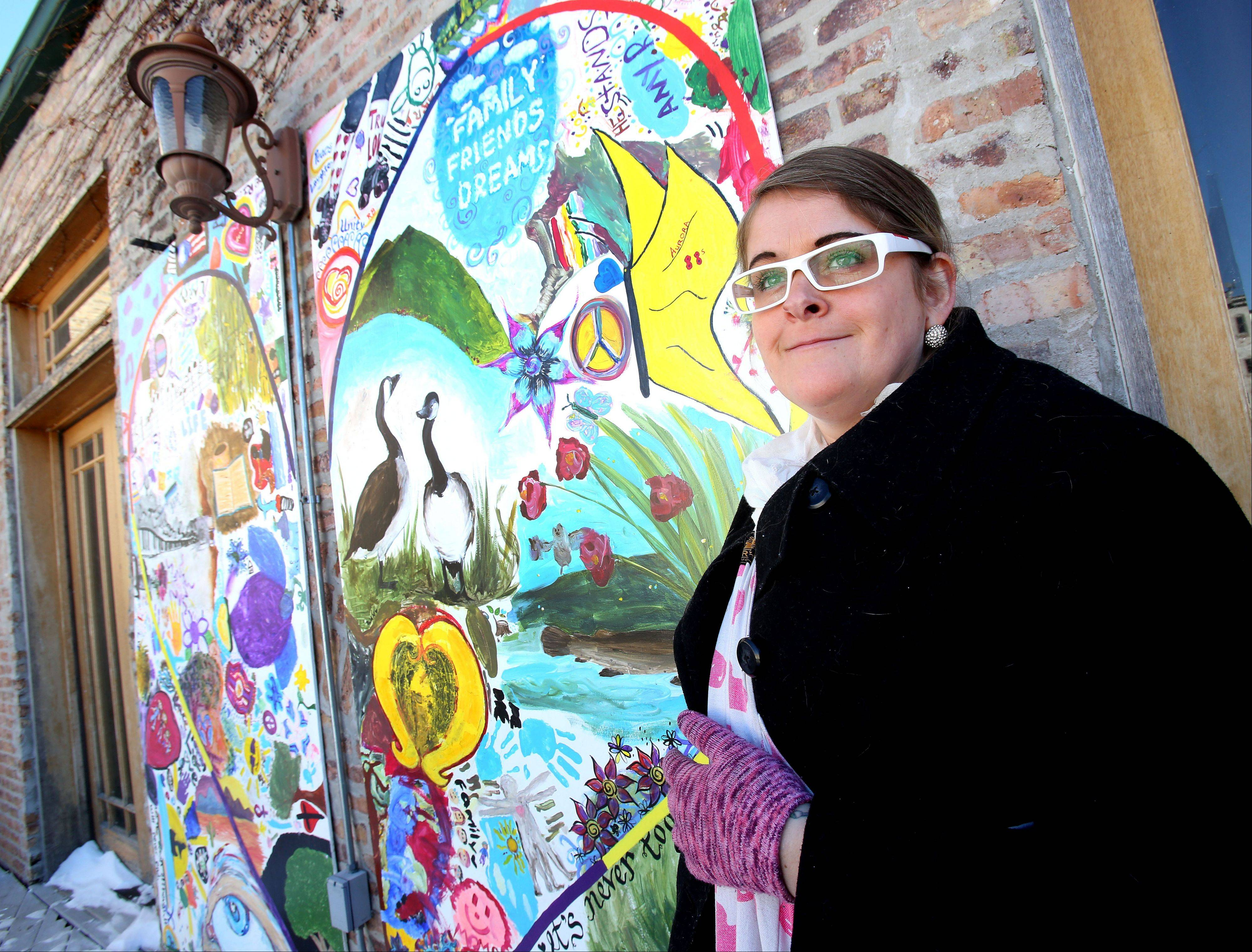 "Melissa Hedlund stands by a ""Mural of Love"" outside of the River Edge Caf� in Aurora. She had 100 people contribute to two panels of the mural with the directive to draw what they love. A bucket of chalk sits in front of the third panel so anyone can add to it."