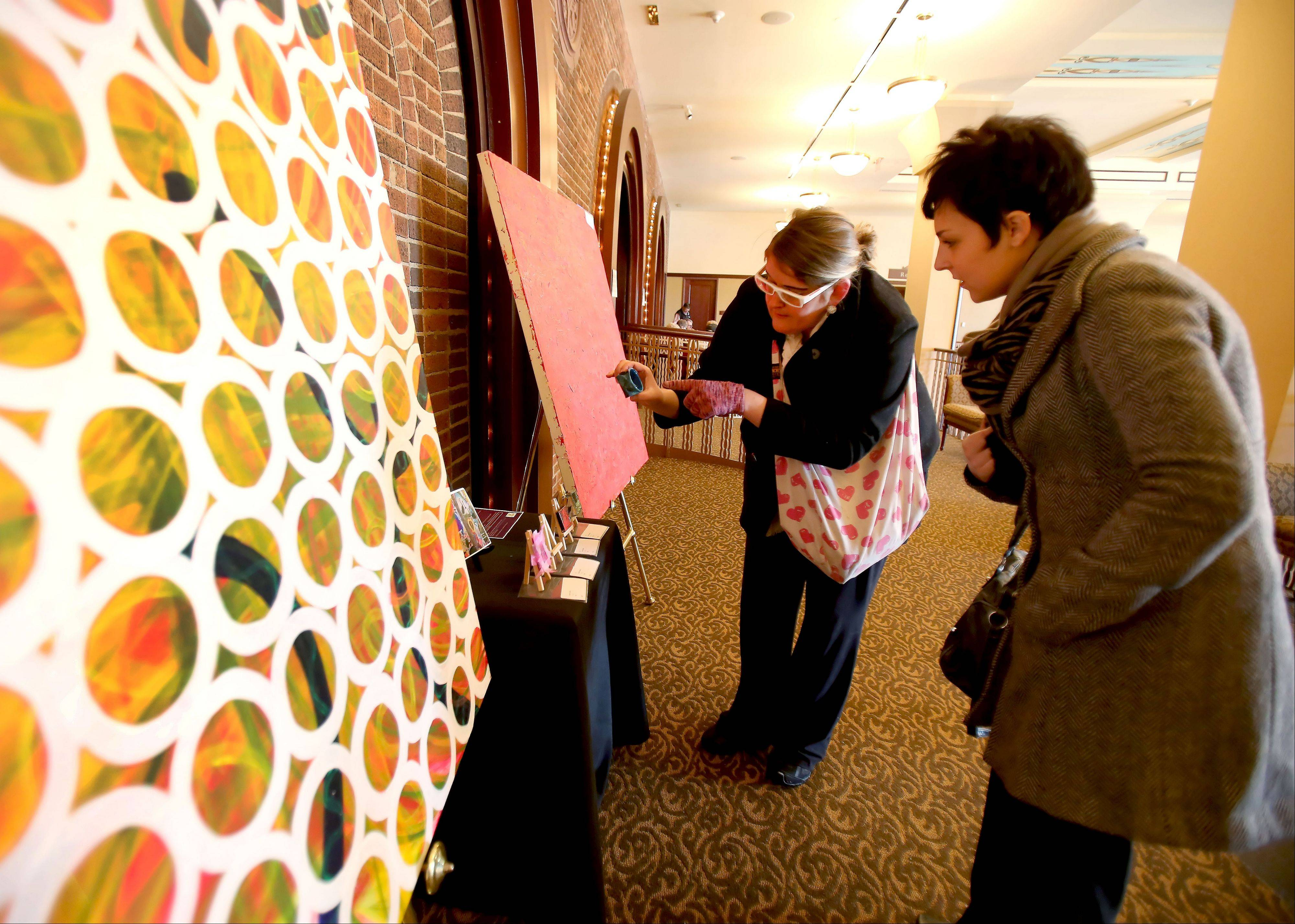 Melissa Hedlund shows Lisa Kolodziej, right, art she has had on display at the Paramount Theatre in Aurora. A fan of acrylics, Hedlund spends only about five hours a month working on her own artwork and devotes the rest of her time art therapy projects.