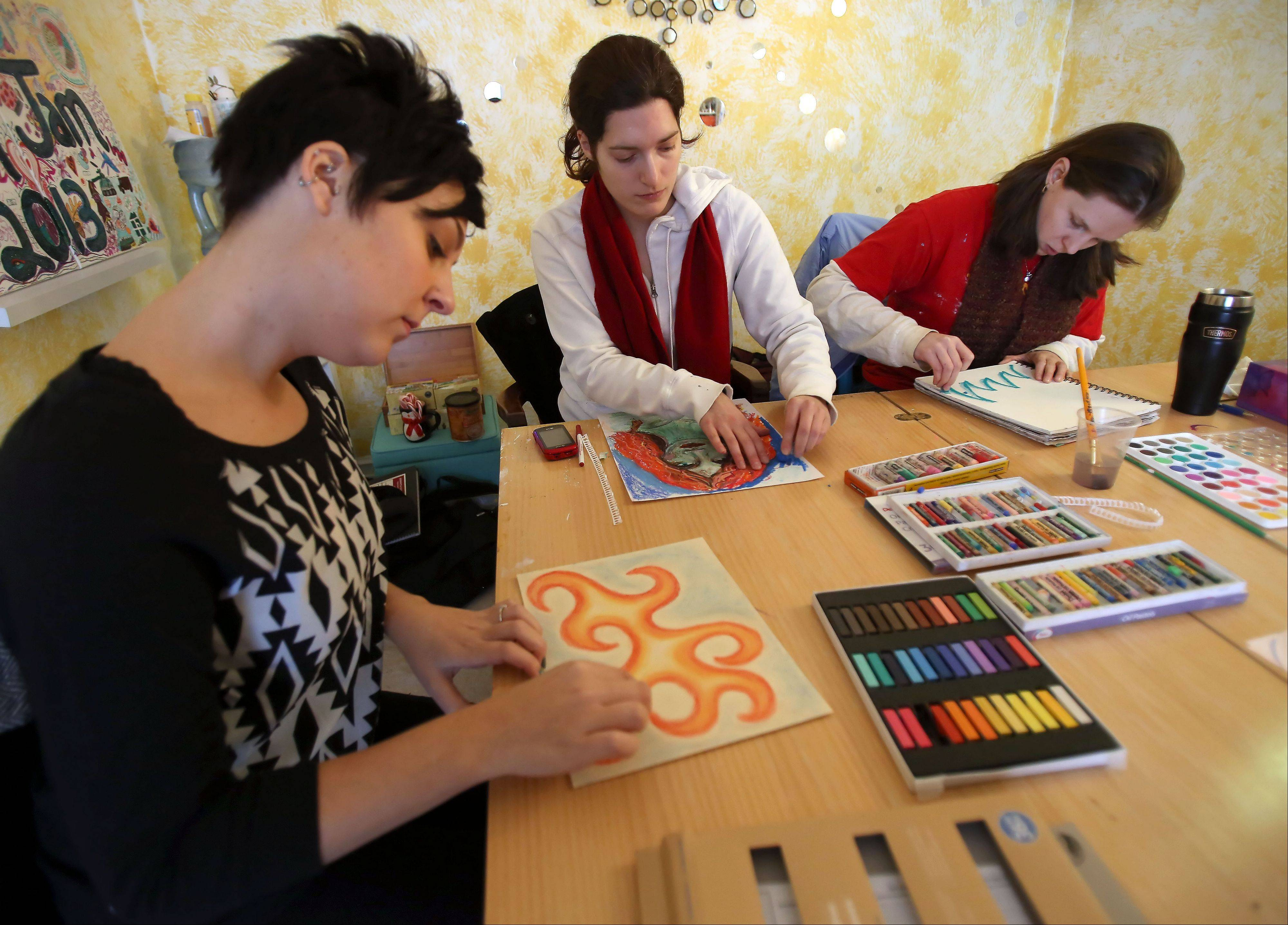 Lisa Kolodziej of Hammond, Ind., Carla DePalma of Glen Ellyn and Briana Colton of Chicago work on pictures in art therapy class led by Melissa Hedlund.