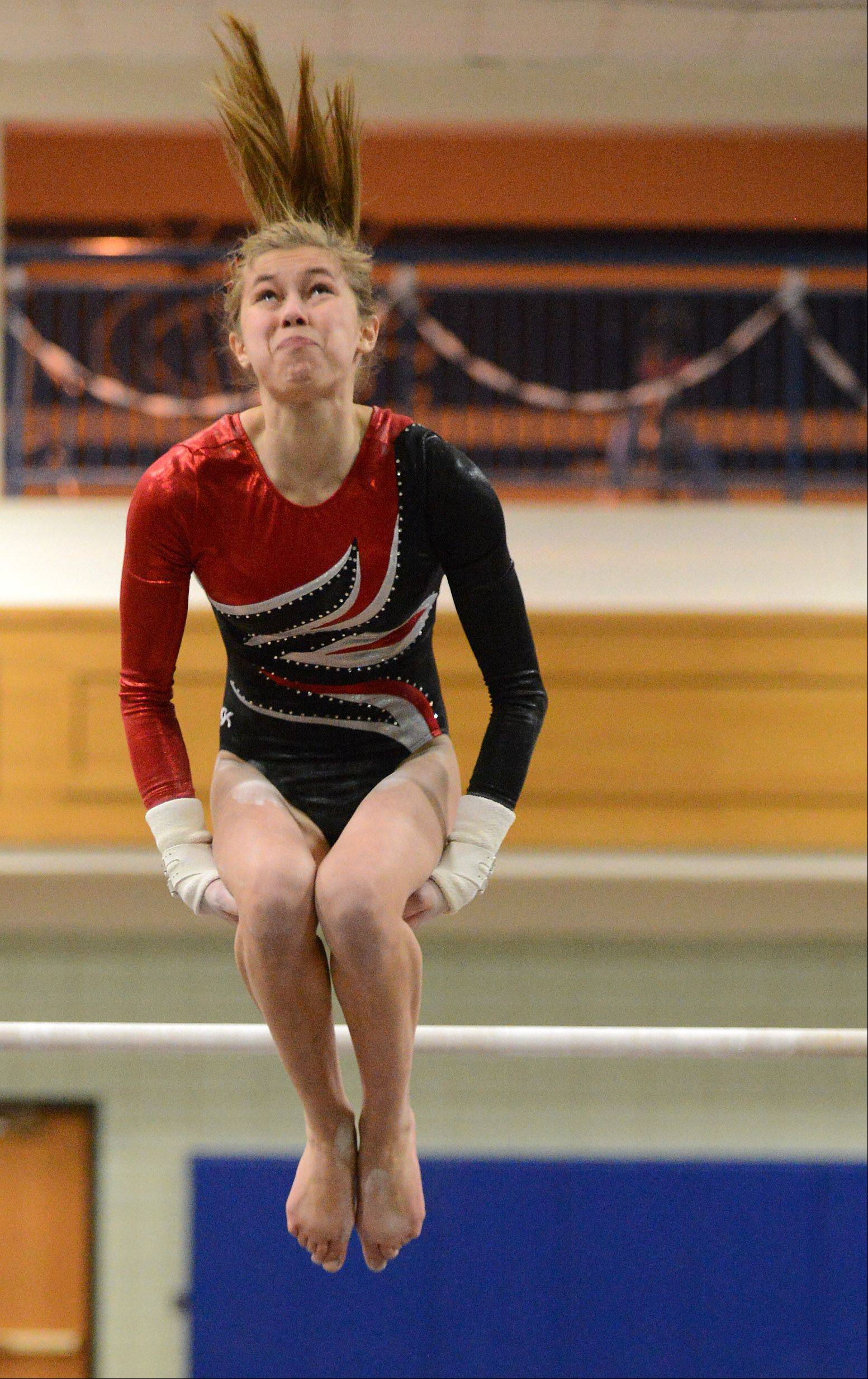 Ashley McKee of the U46 coop team dismounts during the uneven parallel bars during regional gymnastics action at Geneva High School Thursday.