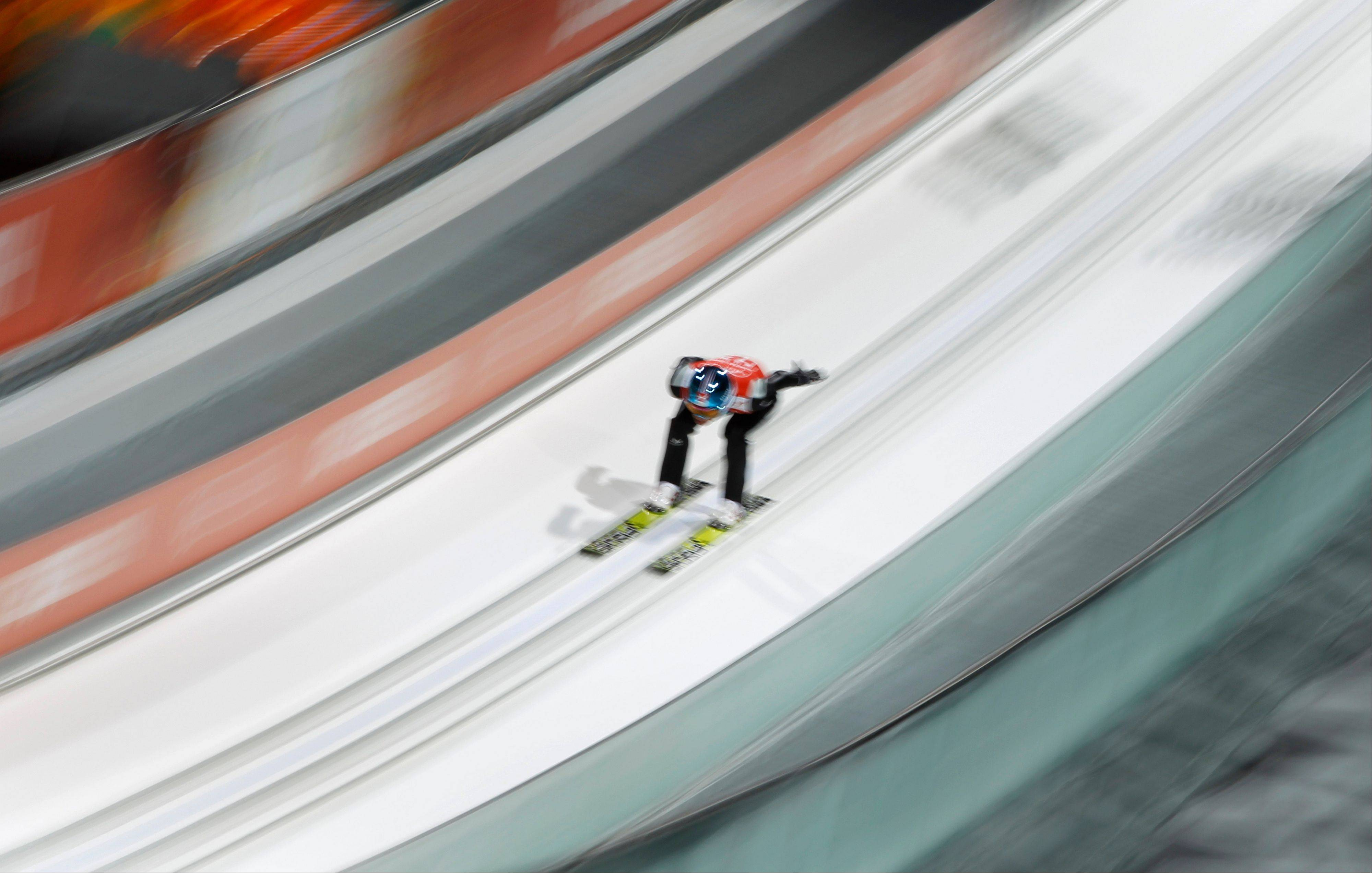 An unidentified athlete makes an attempt in the men's normal hill ski jumping training at the 2014 Winter Olympics, Thursday, Feb. 6, 2014, in Krasnaya Polyana, Russia.
