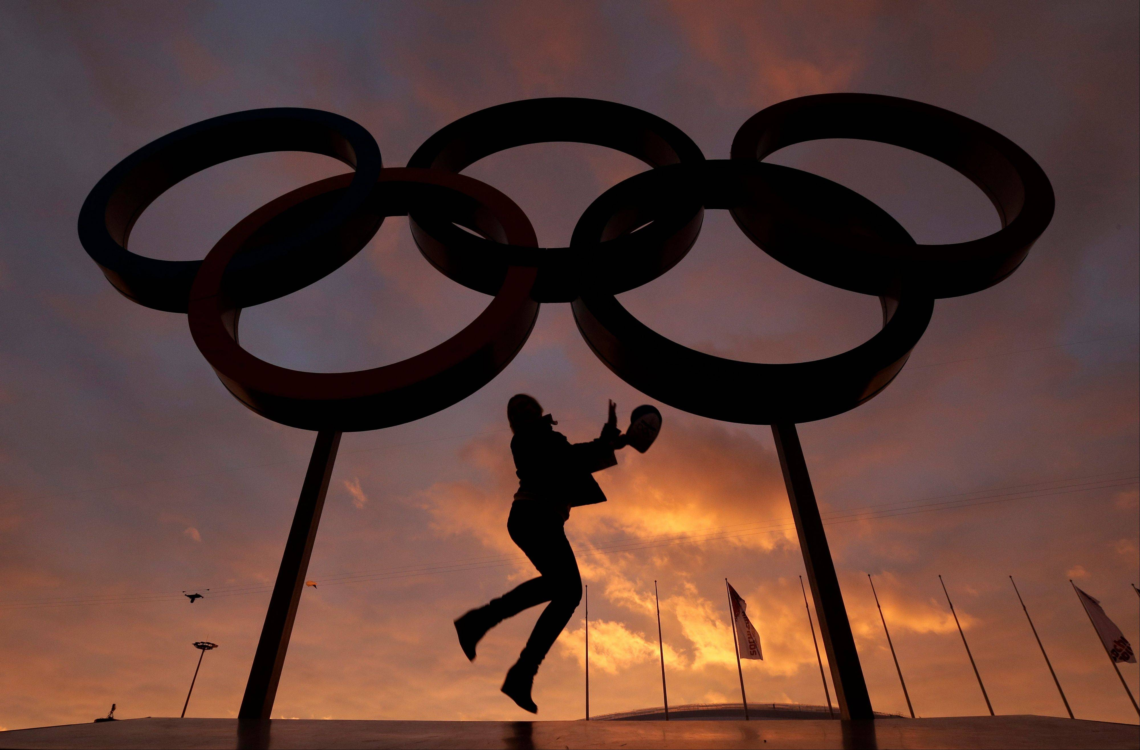 A woman poses for a photo with the Olympic rings in Olympic Park as preparations continue for the 2014 Winter Olympics in Sochi, Russia on Wednesday, Feb. 5, 2014.