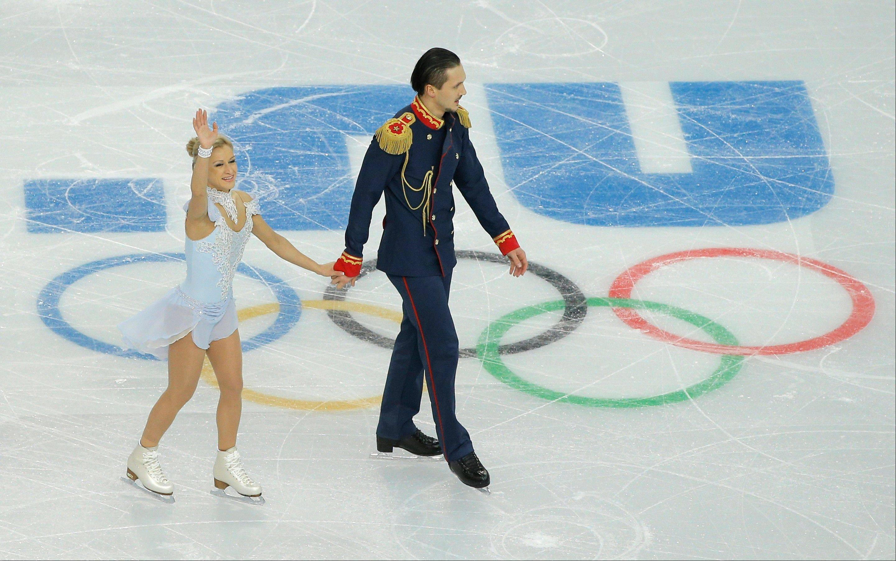 Tatiana Volosozhar, left, waves to spectators after she and Maxim Trankov of Russia competed in the team pairs short program figure skating competition at the Iceberg Skating Palace during the 2014 Winter Olympics.