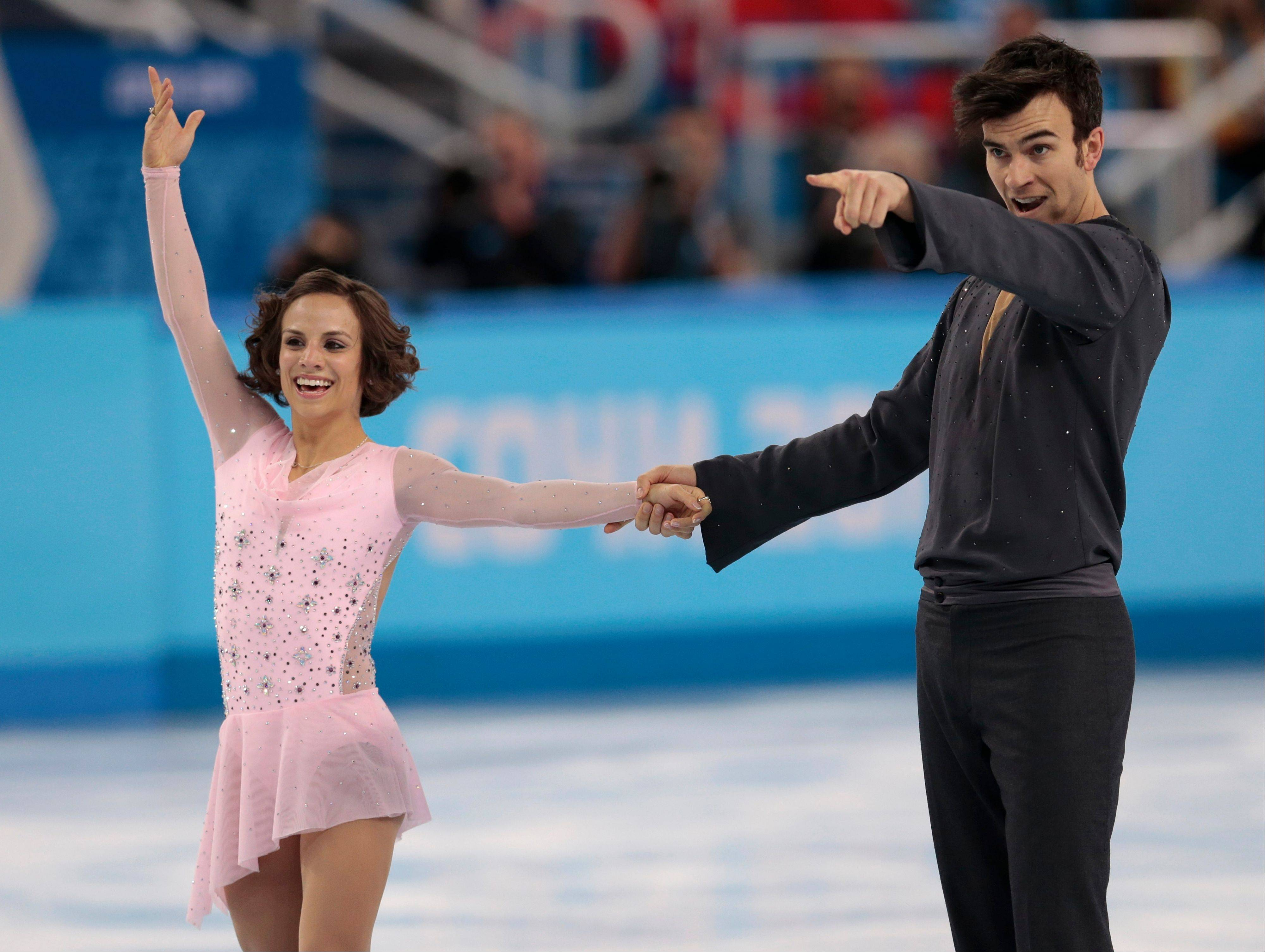 Meagan Duhamel and Eric Radford of Canada gesture after competing in the team pairs short program figure skating competition at the Iceberg Skating Palace during the 2014 Winter Olympics.