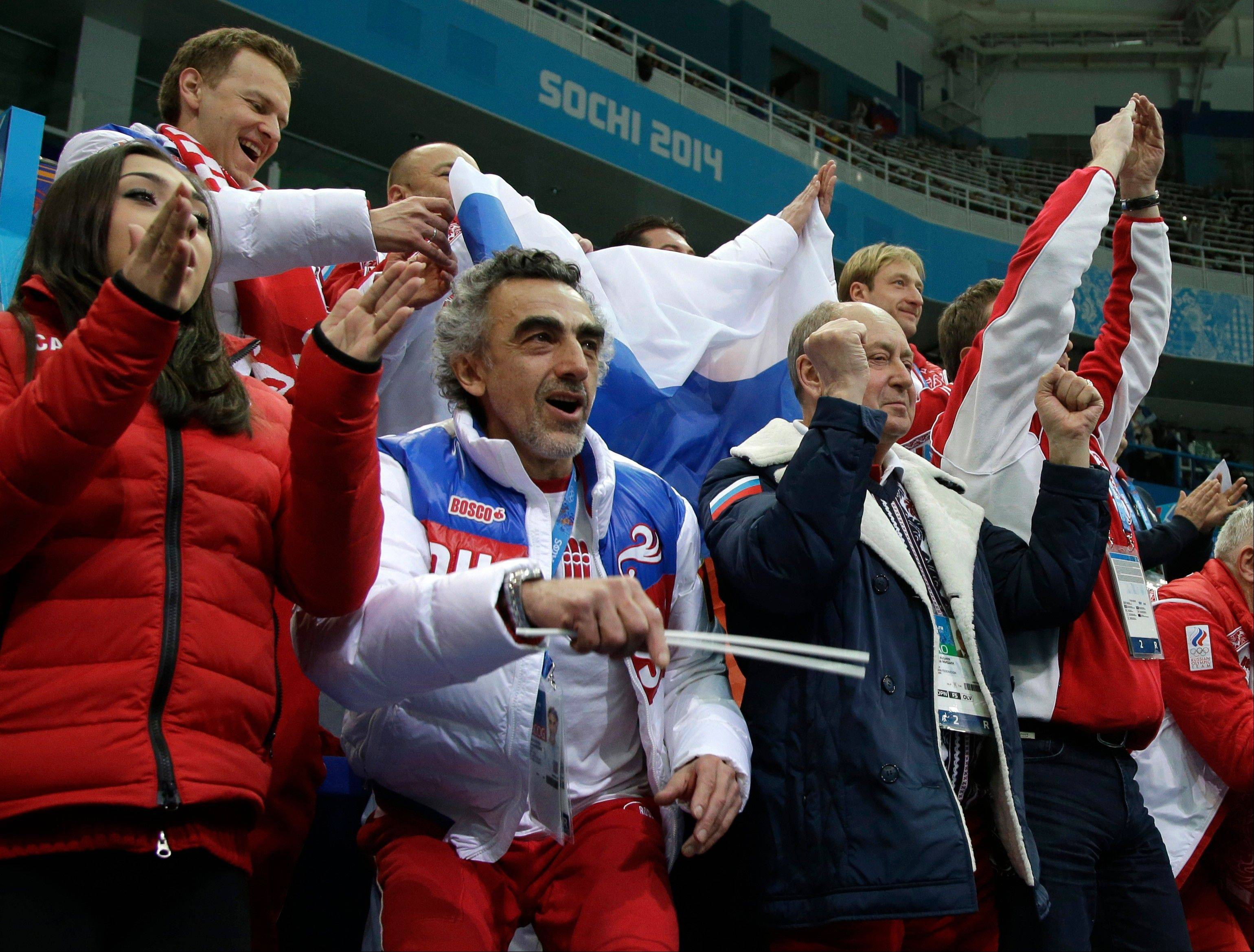Russian team members cheer for Tatiana Volosozhar and Maxim Trankov of Russia during the team pairs short program figure skating competition at the Iceberg Skating Palace during the 2014 Winter Olympics.