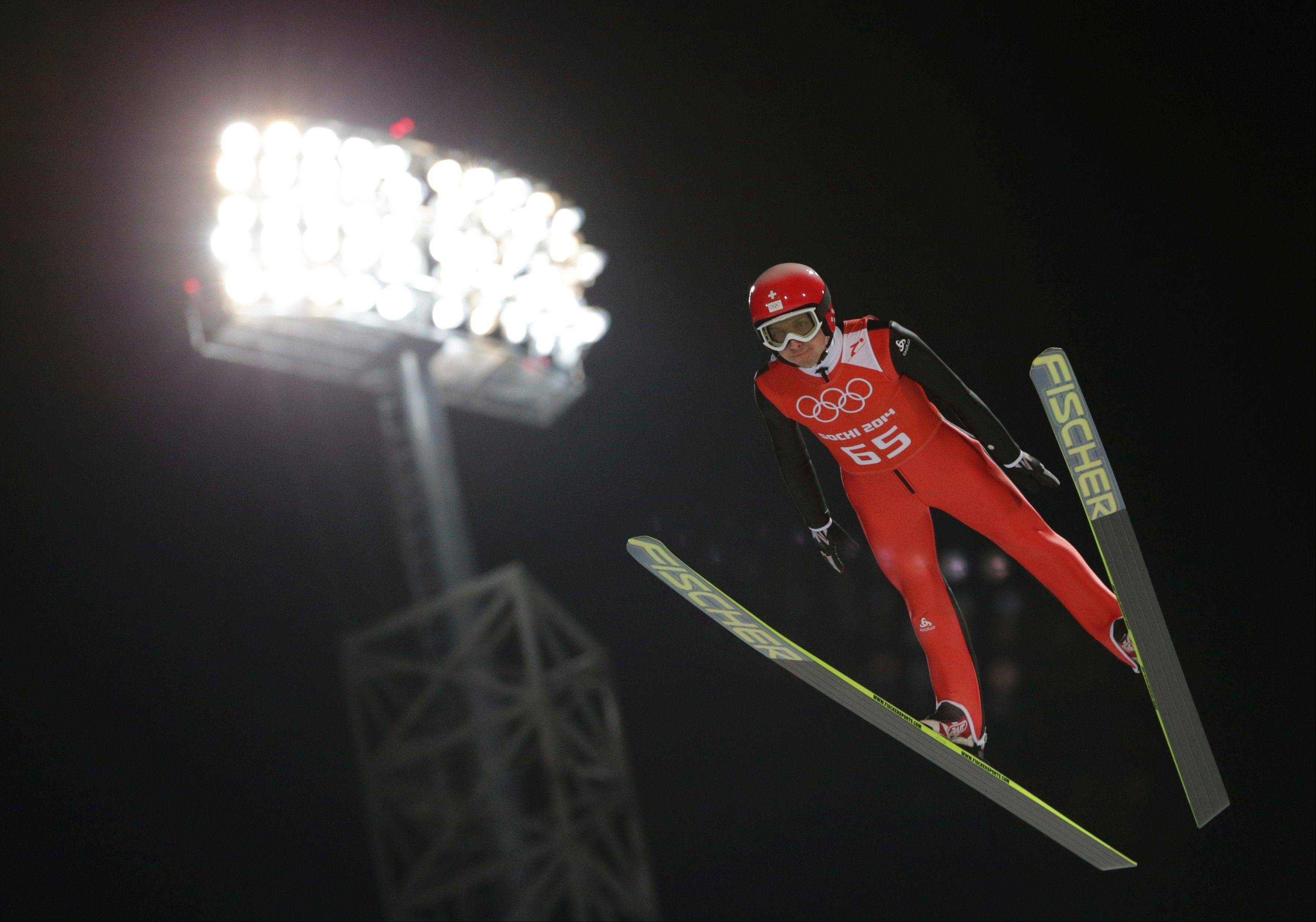 Switzerland's Simon Ammann makes an attempt from the normal hill during the men's ski jumping training at the 2014 Winter Olympics, Thursday, Feb. 6, 2014, in Krasnaya Polyana, Russia.