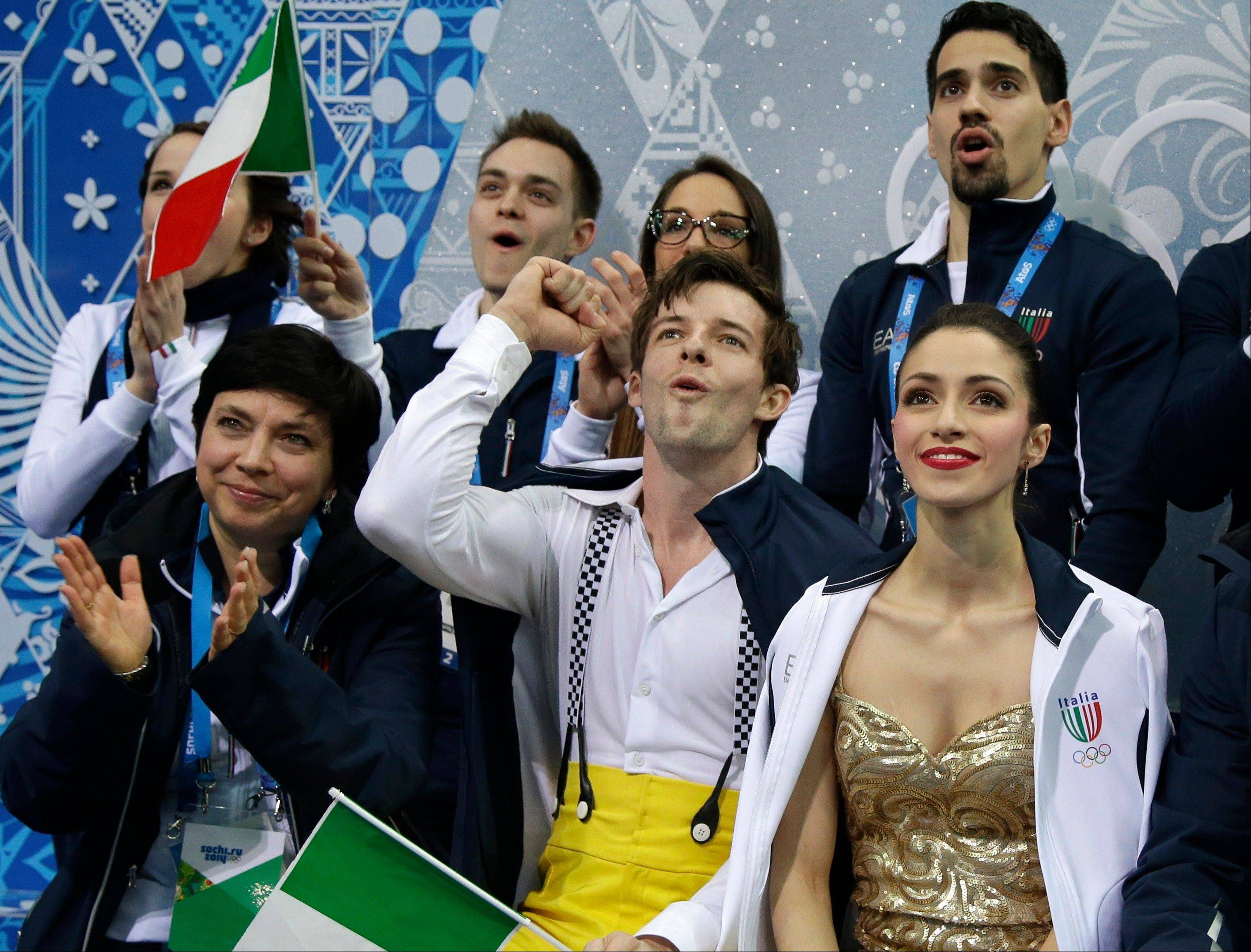 Stefania Berton and Ondrej Hotarek of Italy, front right, wait for their results for the team pairs short program figure skating competition at the Iceberg Skating Palace during the 2014 Winter Olympics.