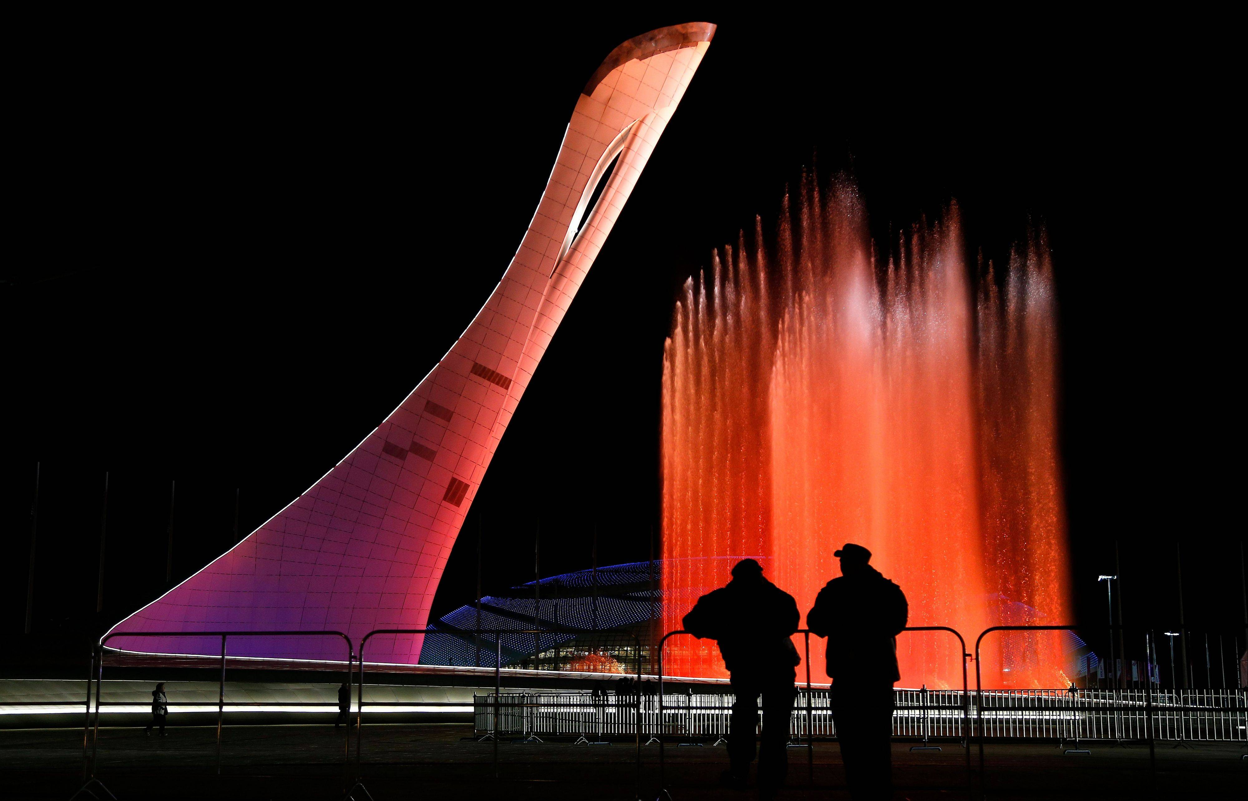 "Security personnel watch a practice run of a fountain show to music from ""Swan Lake"" on the perimeter of the Olympic cauldron in preparation for the 2014 Winter Olympics."