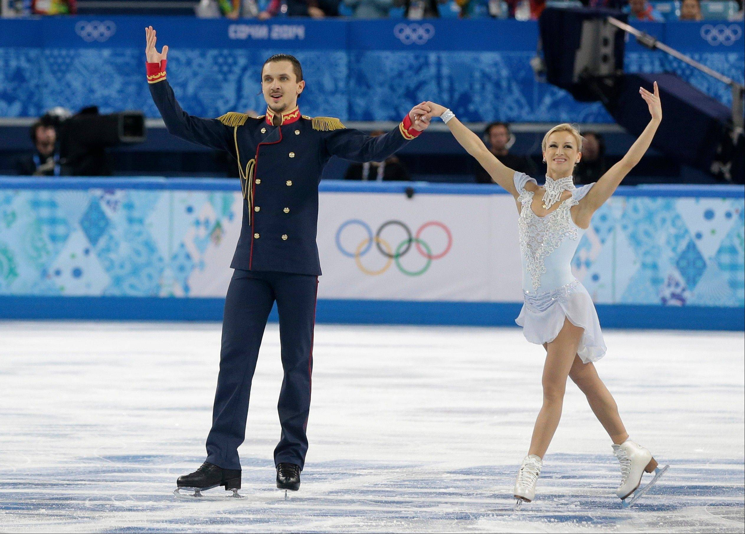 Tatiana Volosozhar and Maxim Trankov of Russia gesture to the crowd after finishing their routine in the team pairs short program figure skating competition at the Iceberg Skating Palace.