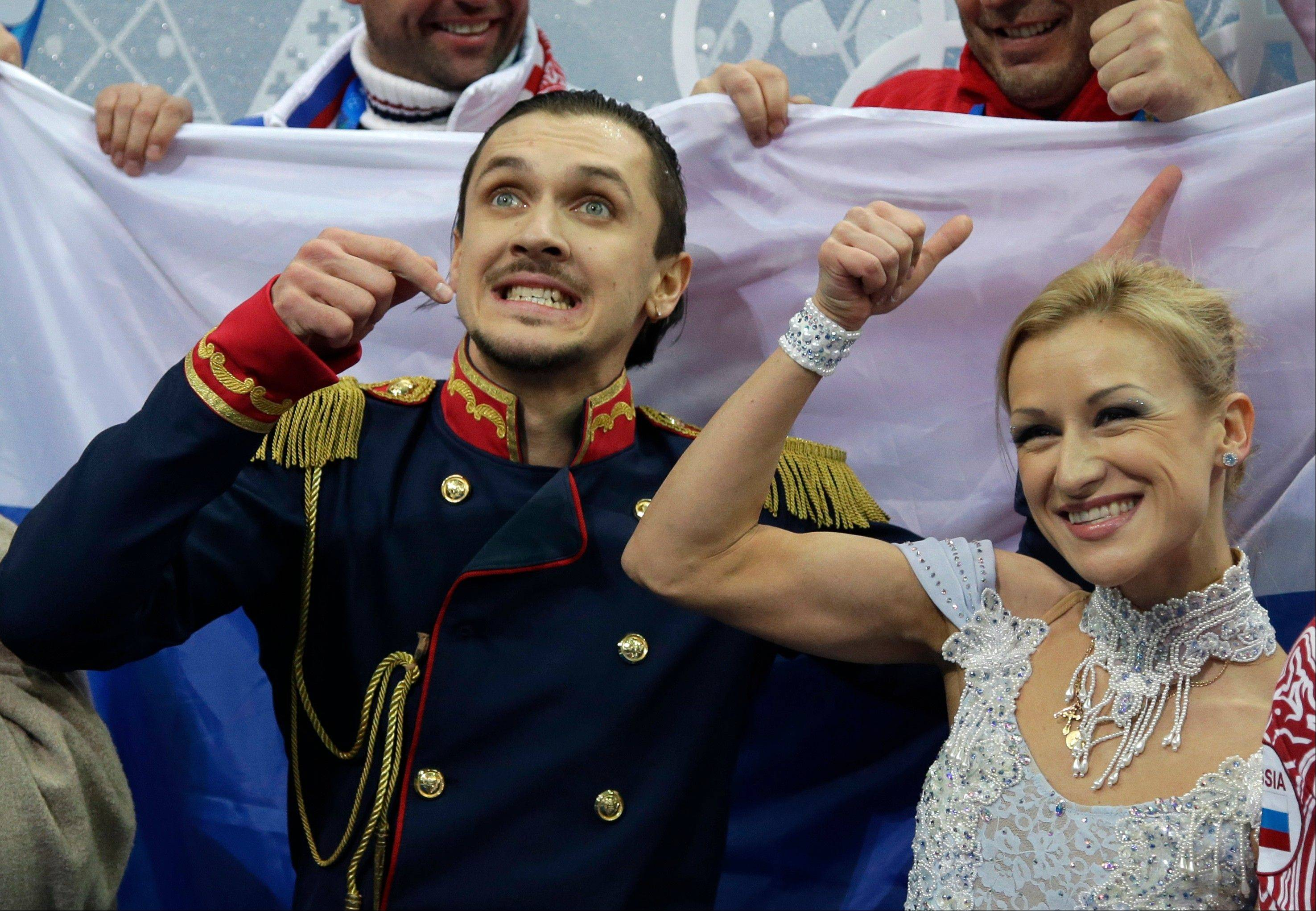 Tatiana Volosozhar and Maxim Trankov of Russia gesture to spectators as they wait for their results in the team pairs short program figure skating competition at the Iceberg Skating Palace.