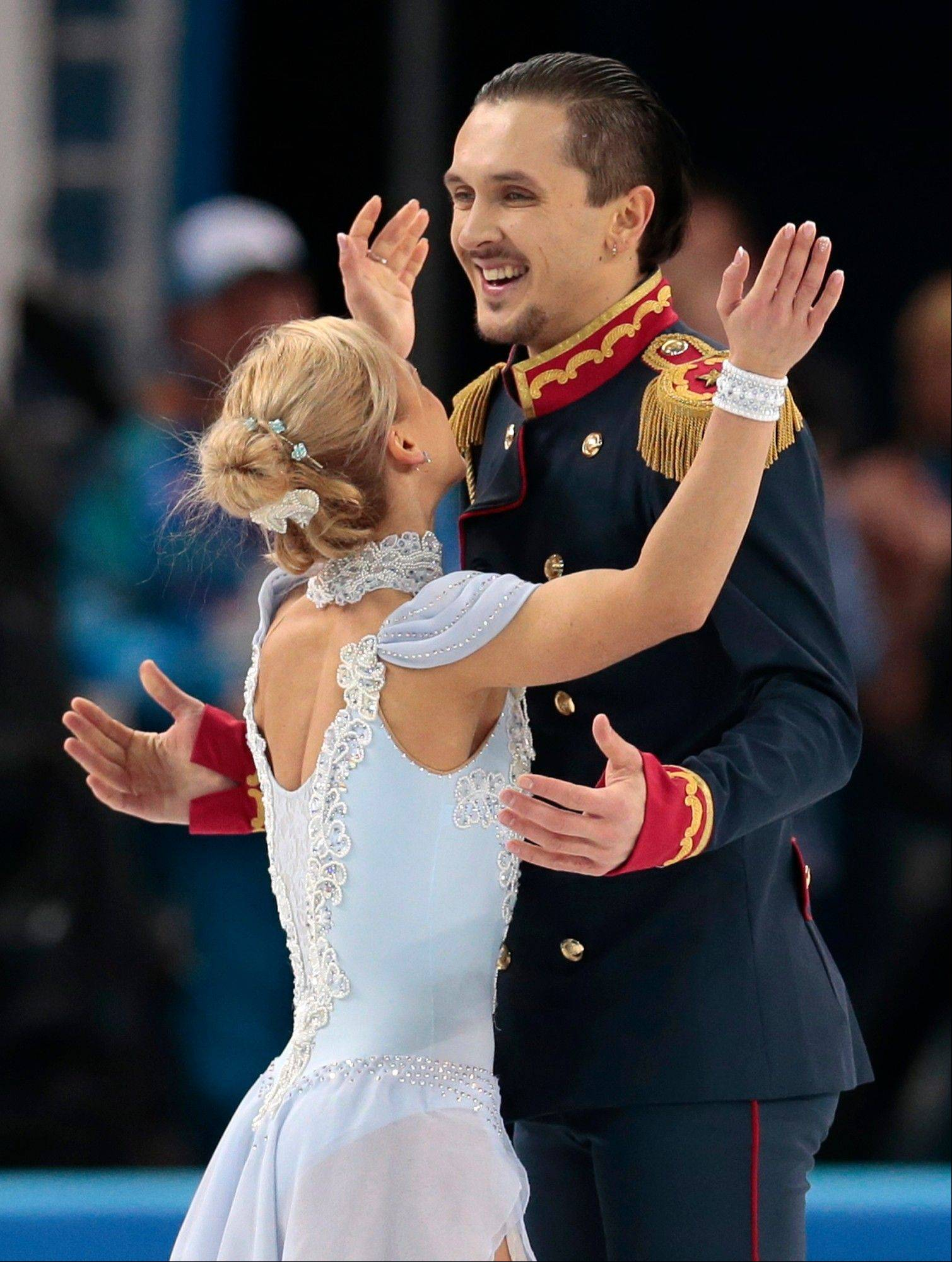 Tatiana Volosozhar and Maxim Trankov of Russia embrace after competing in the team pairs short program figure skating competition at the Iceberg Skating Palace during the 2014 Winter Olympics.