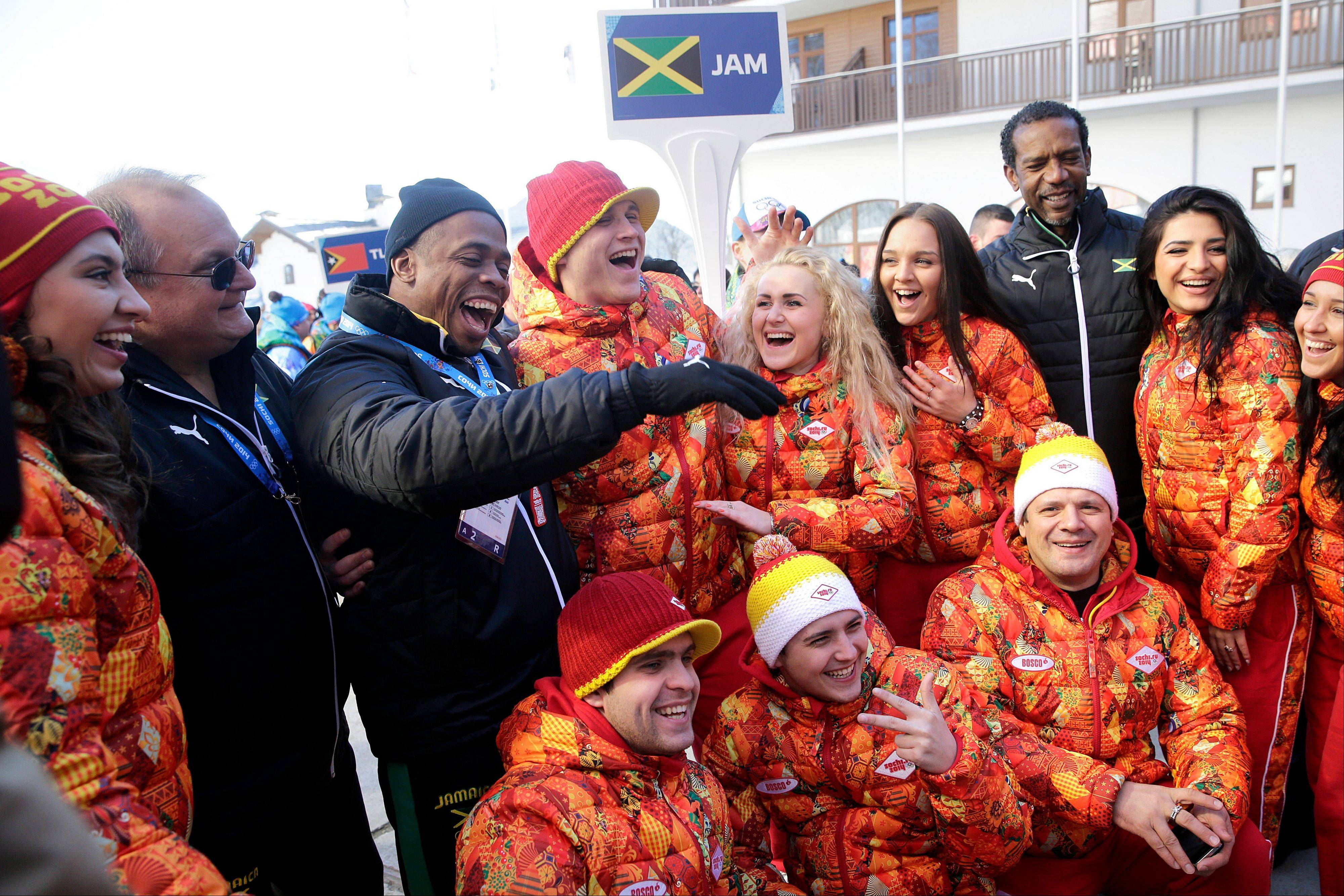 Members of Jamaican Olympic team, including bobsled brakeman Marvin Dixon, third from left, and coach Paul Skog, second from left, pose Thursday with the Choir of Siberia after a welcome ceremony at the Mountain Olympic Village prior to the 2014 Winter Olympics.