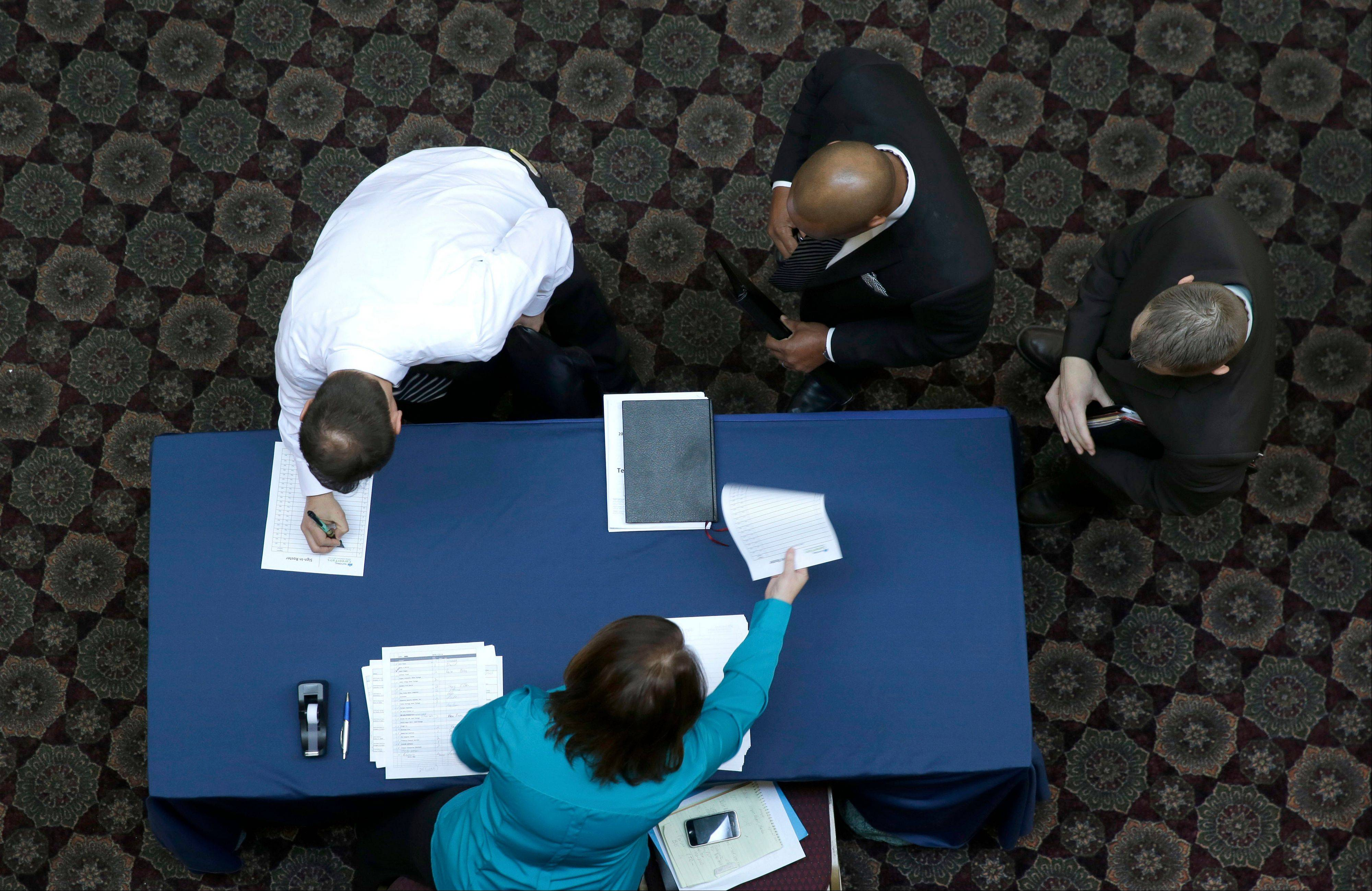 Job seekers sign in before meeting prospective employers during a career fair at a hotel in Dallas. The number of people applying for U.S. unemployment benefits declined 20,000 last week to 331,000, suggesting that Americans are facing fewer layoffs and better job prospects.