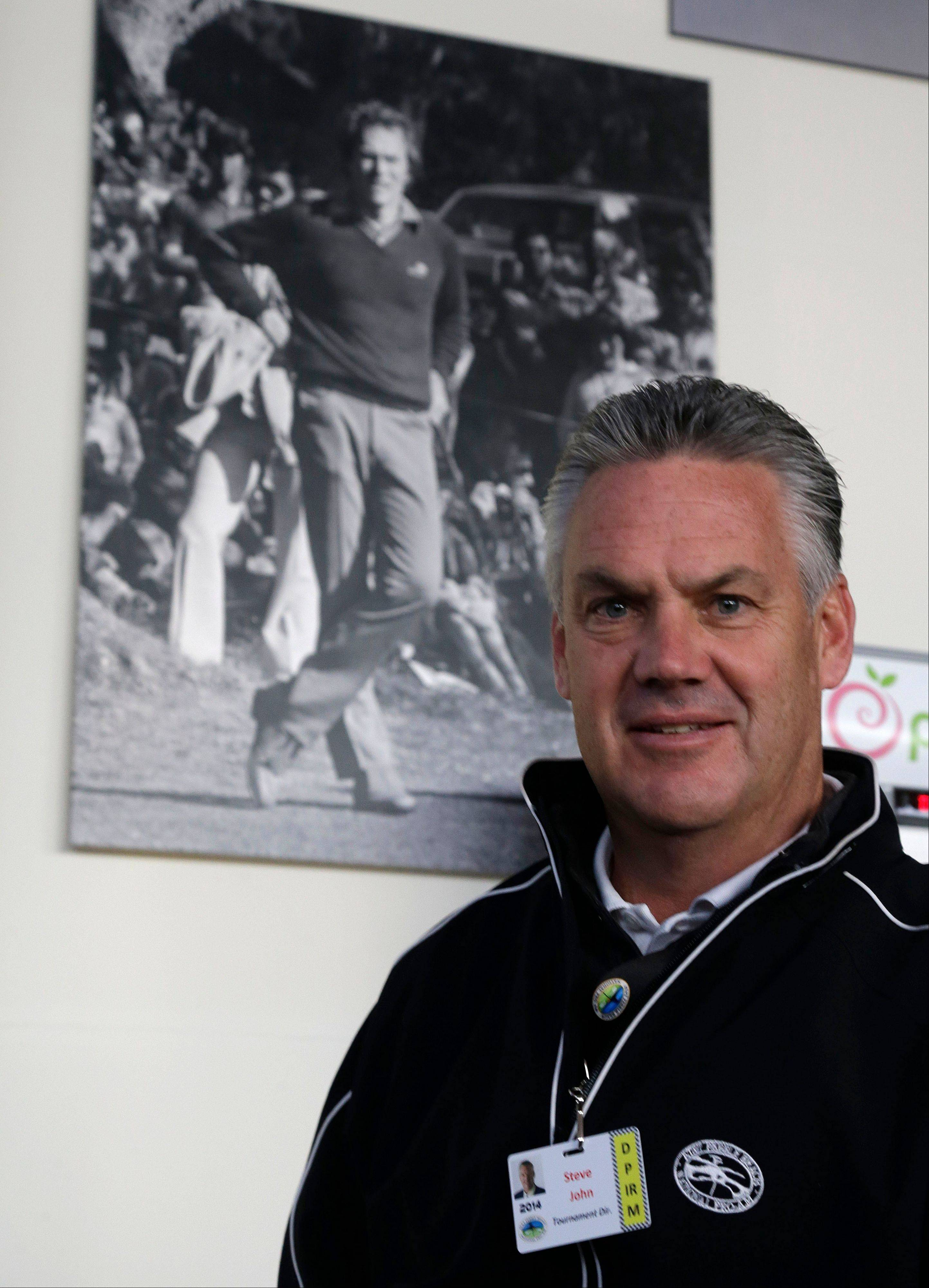 Steve John, CEO of the Monterey Peninsula Foundation and tournament director of the AT&T Pebble Beach Pro-Am golf tournament, stands beneath a photograph of Clint Eastwood Friday in Pebble Beach, Calif. John was choking on a piece of cheese at a volunteer party when Eastwood gave him the Heimlech maneuver.