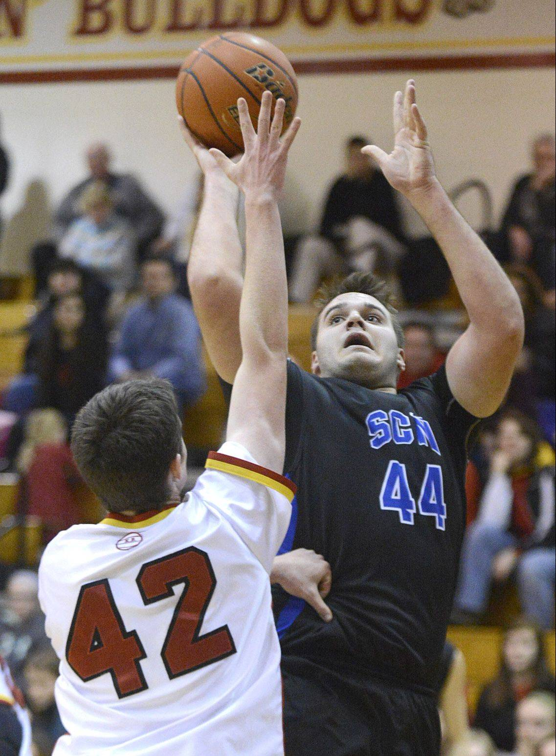 St. Charles North�s Chase Gianacakos shoots over Batavia�s Ryan Olson in the second quarter on Friday in Batavia.