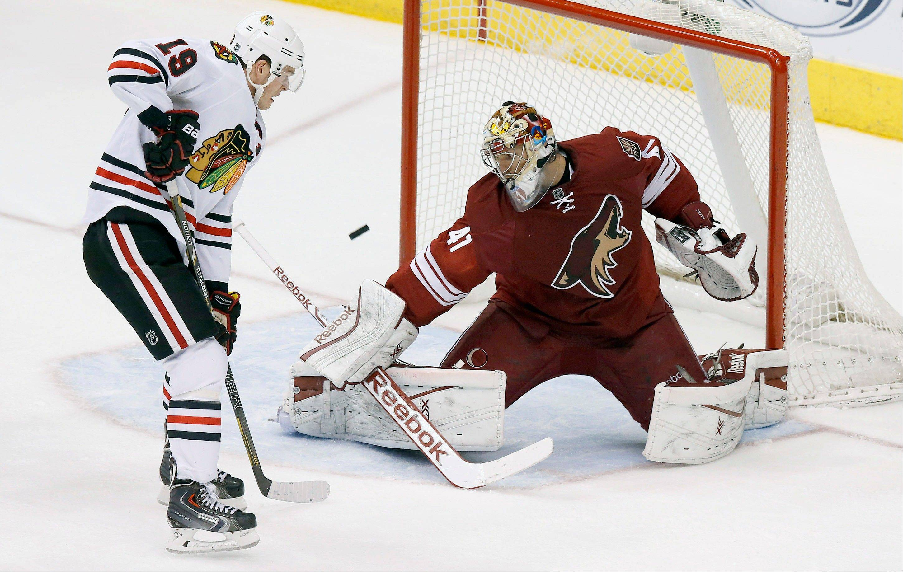 Phoenix Coyotes' Mike Smith (41) makes a save on a rebound shot by Chicago Blackhawks' Jonathan Toews (19) during the second period in an NHL hockey game, Friday Feb. 7, 2014, in Glendale, Ariz. (AP Photo/Ross D. Franklin)