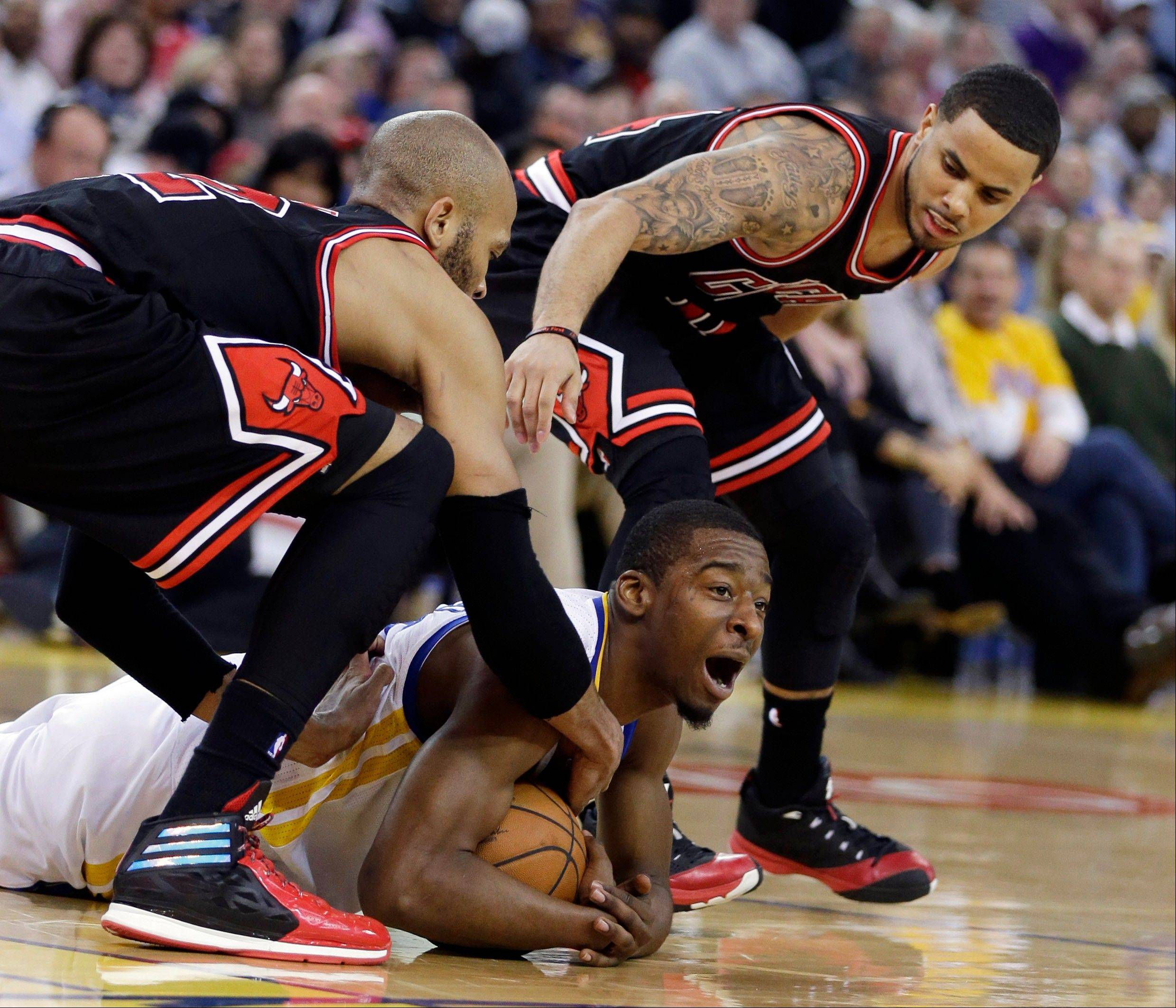 Golden State Warriors' Jordan Crawford, center, fights for a loose ball against Taj Gibson, left, and D.J. Augustin of the bulls in Thursday's NBA game in Oakland, Calif. Golden State won 102-87.