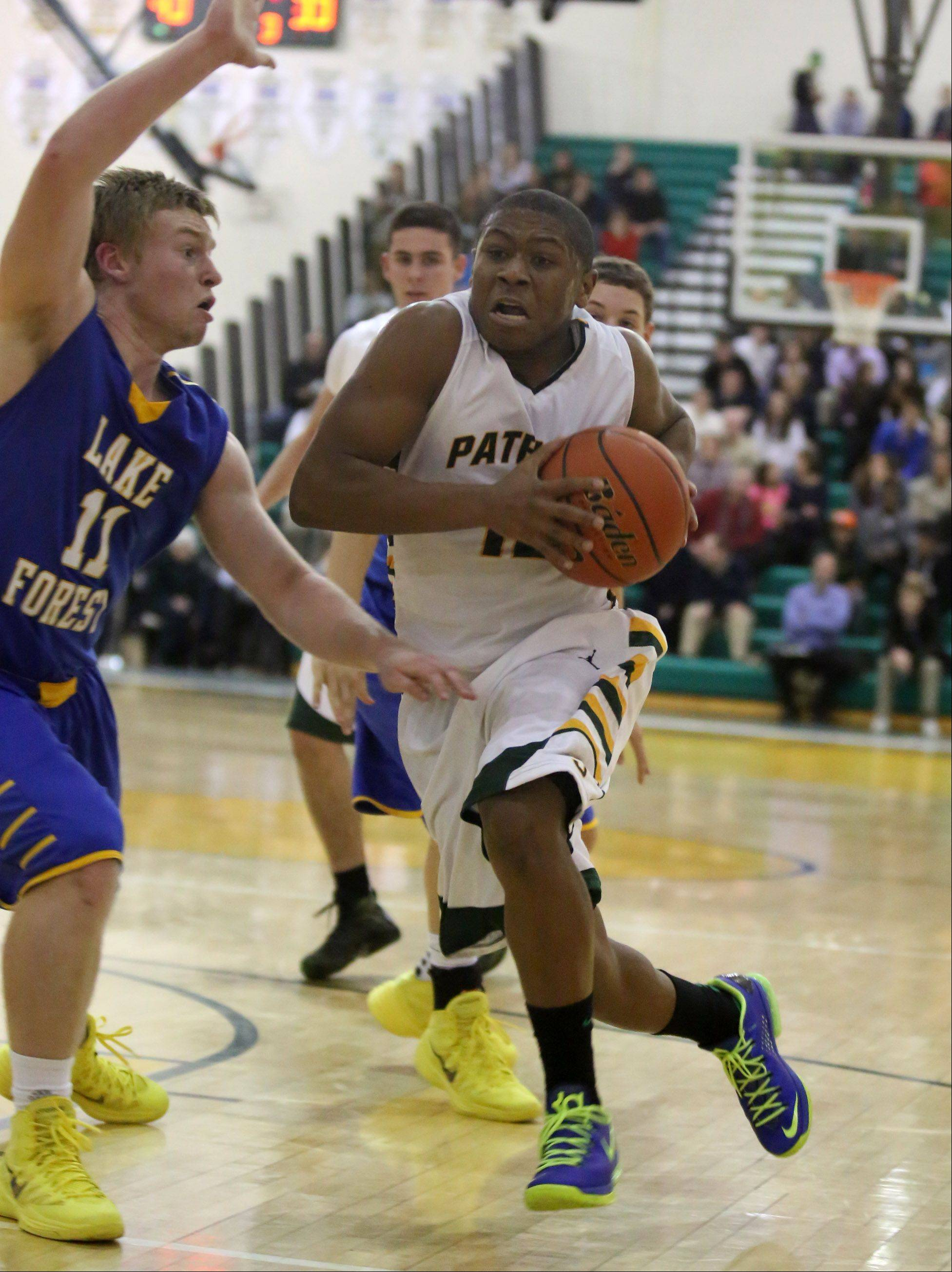 Matt Johnson, here driving to the basket against Lake Forest's Jack Traynor, is showing toughness as he adapts to the loss of his mother and fits in with his new basketball family at Stevenson.