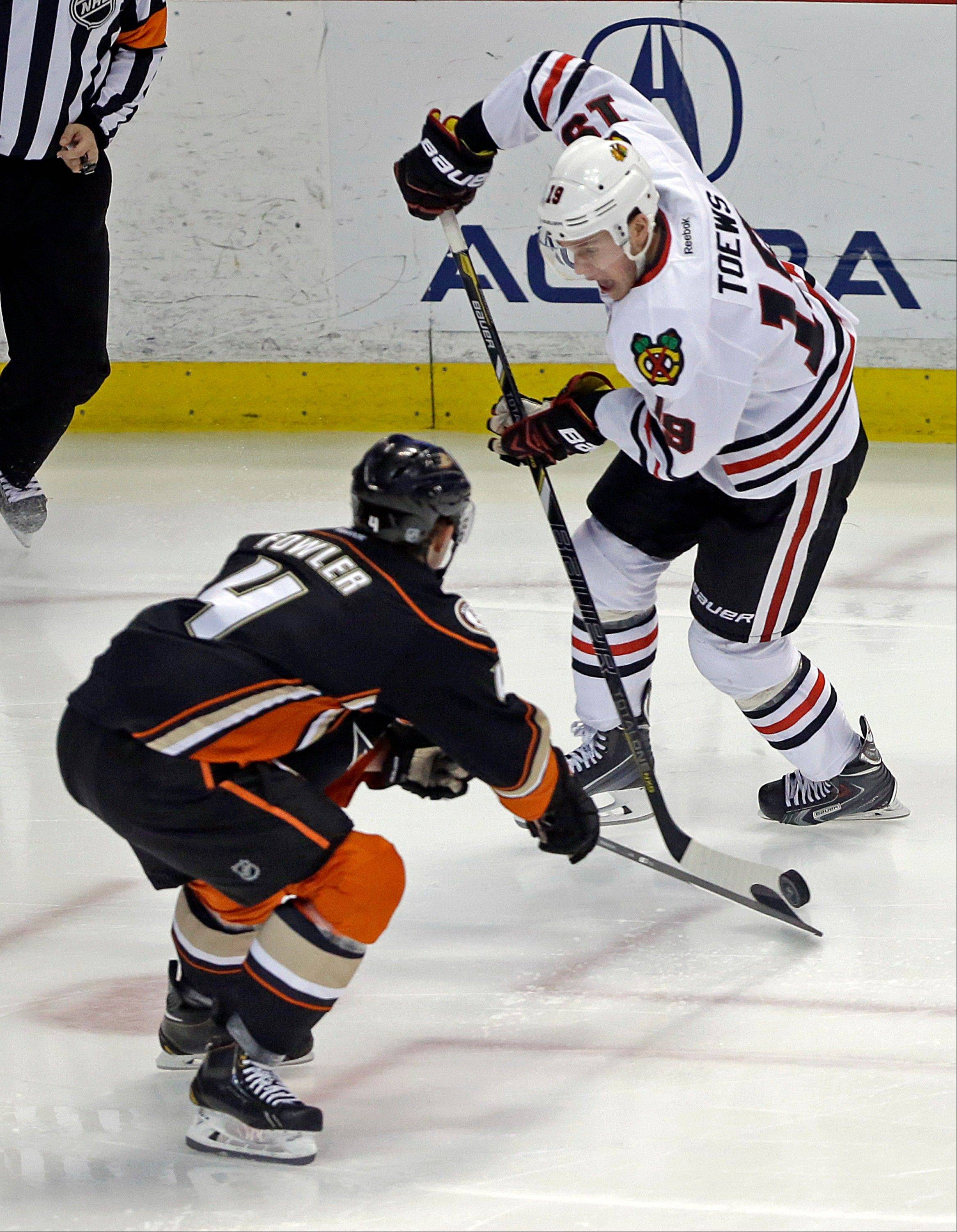 Chicago Blackhawks center Jonathan Toews (19) and Anaheim Ducks defenseman Cam Fowler (4) tangle in the third period of an NHL hockey game in Anaheim, Calif., Wednesday, Feb. 5, 2014. The Blackhawks won, 2-0. (AP Photo/Reed Saxon)