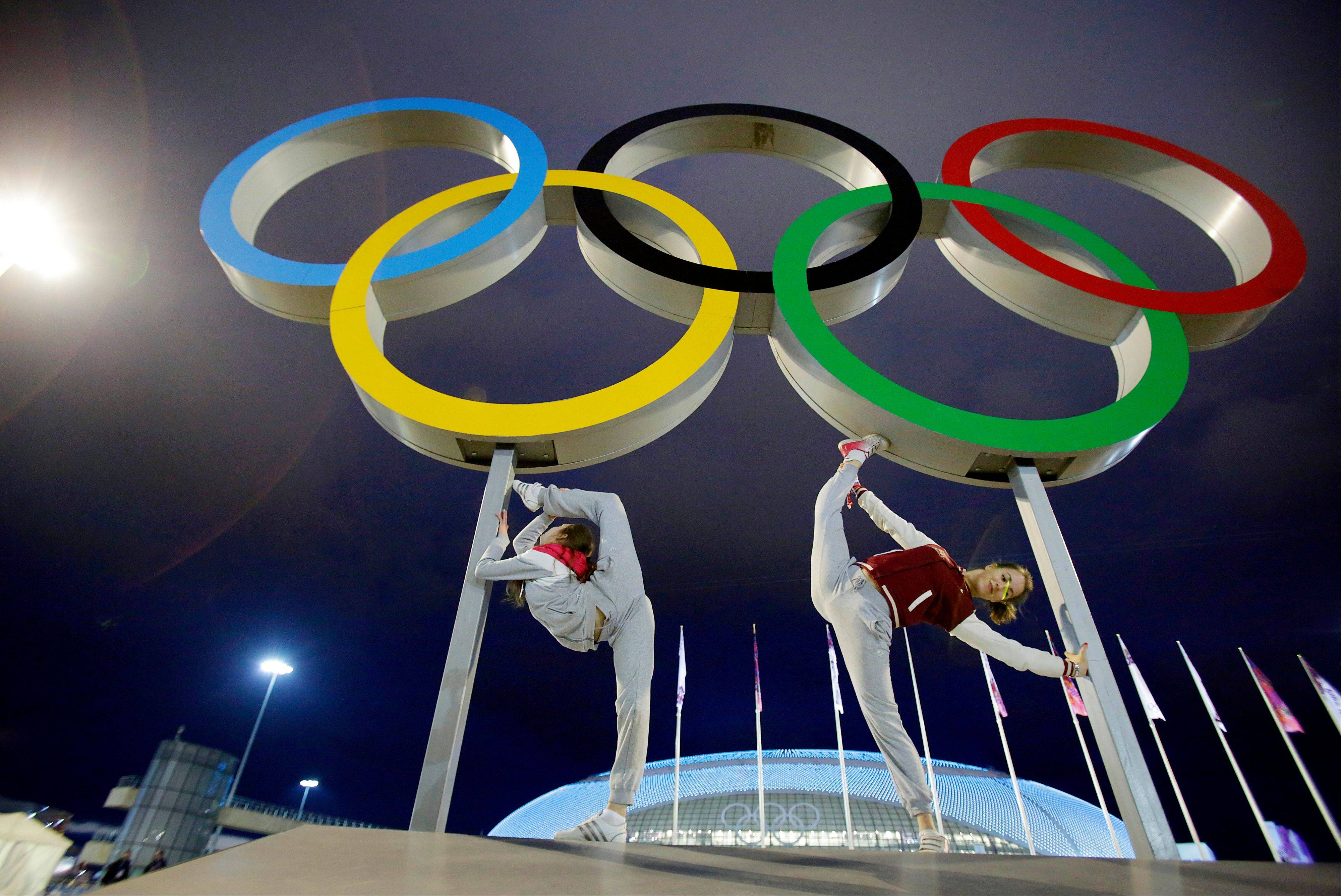Russian dancers who will be performing at the opening ceremony pose with the Olympic rings as their friend photographs them, ahead of the 2014 Winter Olympics, Thursday, Feb. 6, 2014, in Sochi, Russia. (AP Photo/Wong Maye-E)