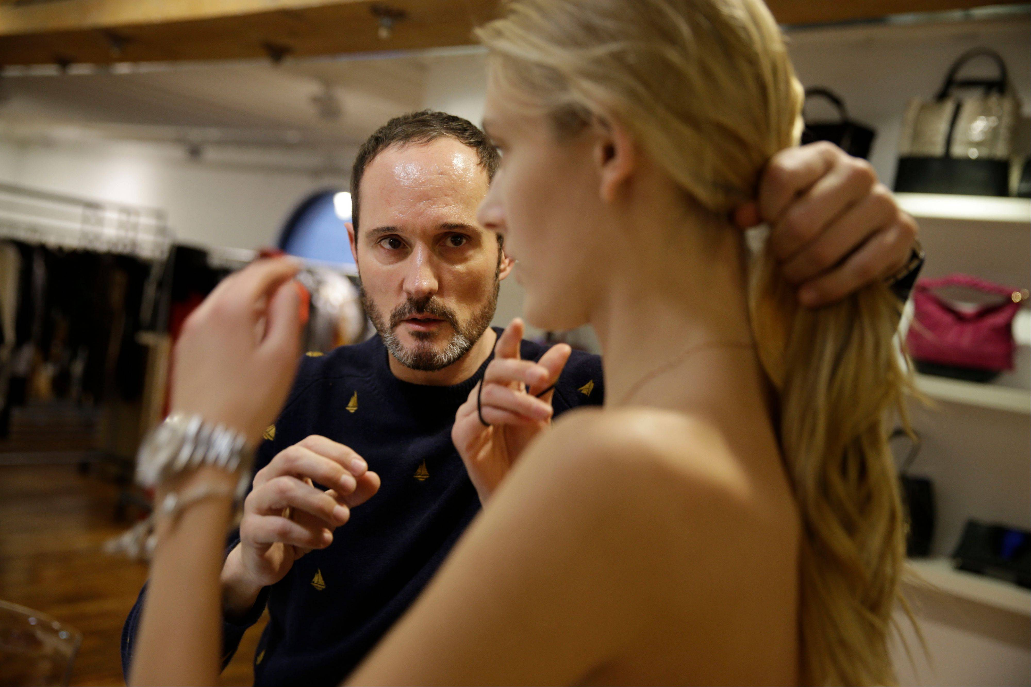 Josep Font, creative director of DelPozo, left, fixes a model's hair during a model casting in New York.