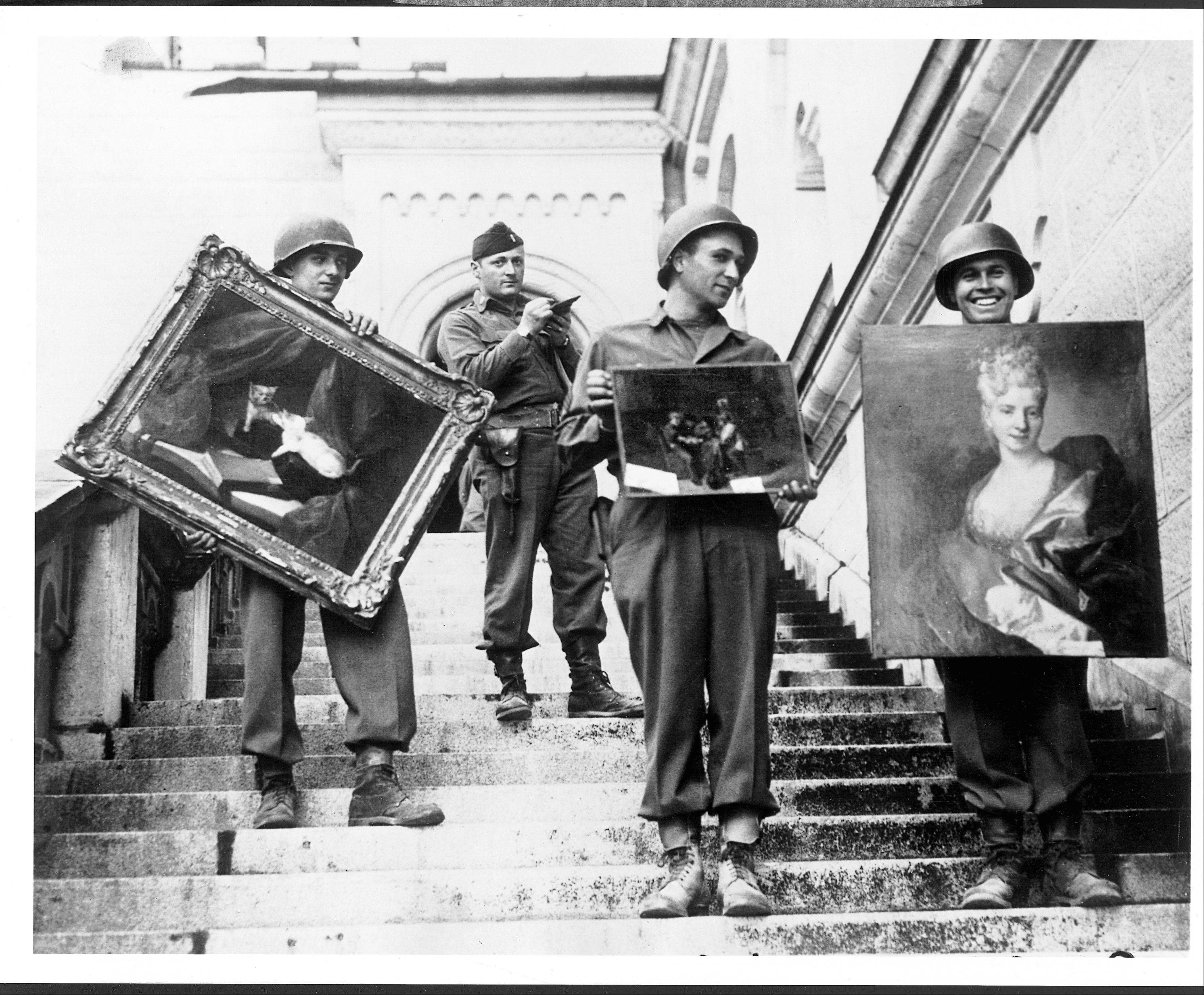 Monuments Man James Rorimer, with notepad, supervises American GI's hand-carrying paintings down the steps of the castle in Neuschwanstein, Germany, in May 1945. The Monuments Men worked to save cultural treasures during World War II.