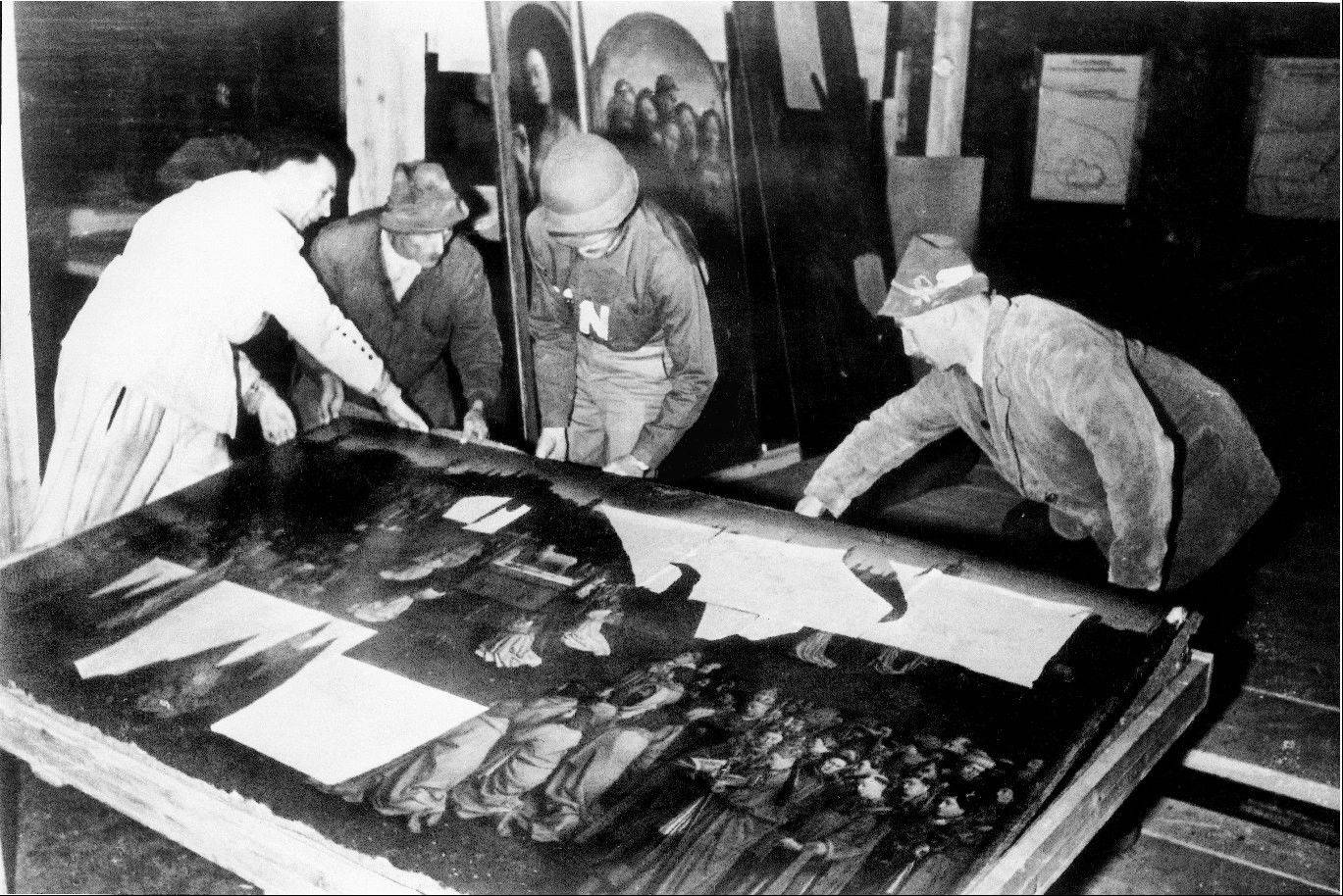 "Monuments Man George Stout, third from left with an ""N"" on his shirt, helps move the central panel of the Ghent Altarpiece in Altaussee, Austria, in July 1945."