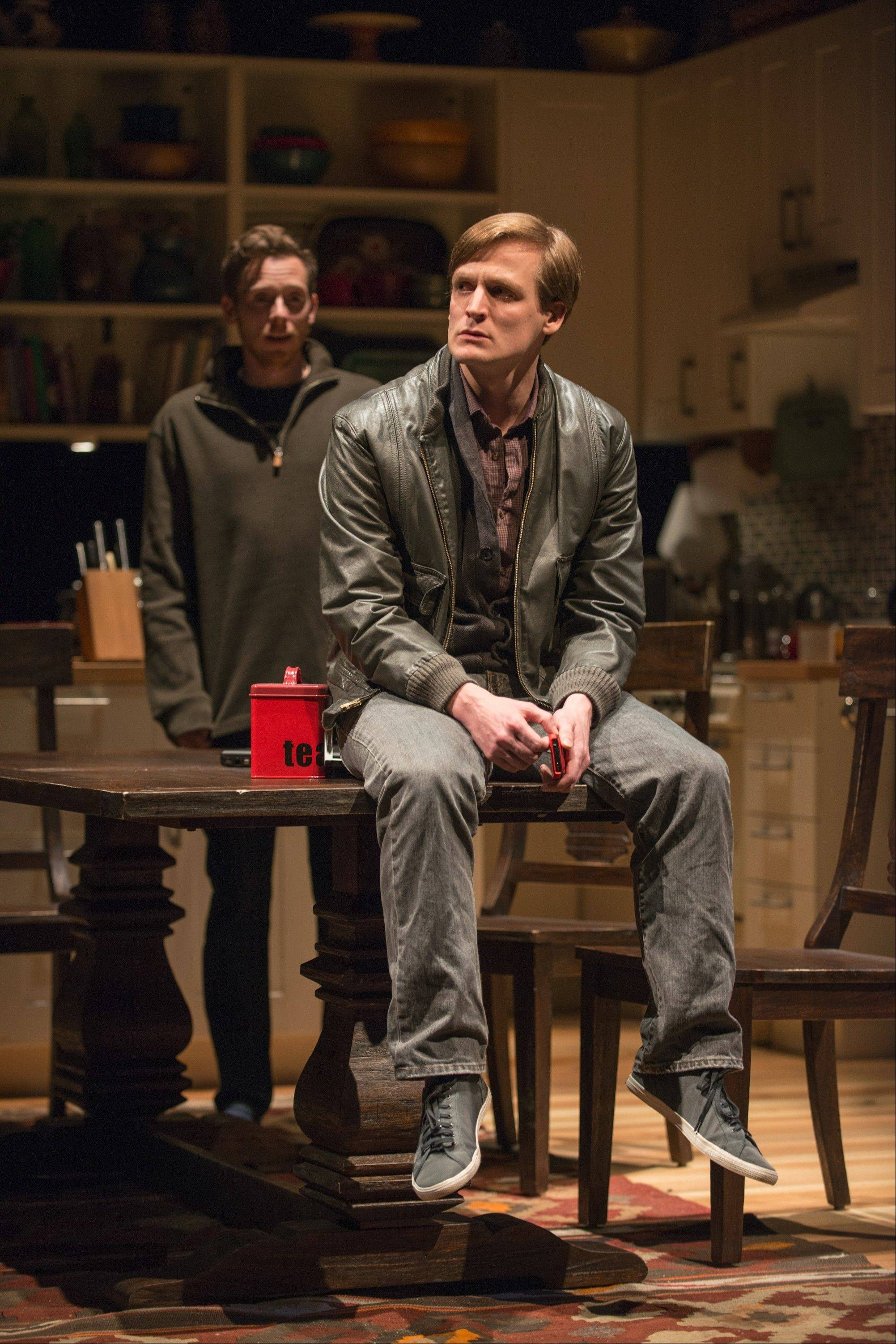 "John McGinty, foreground, plays Billy, a deaf young man whose recent immersion in the Deaf community causes a schism in his family, including older brother Dan (Steve Haggard, background), in Nina Raine's ""Tribes,"" running at Steppenwolf Theatre. Discounted tickets are available for Chicago Theatre Week."