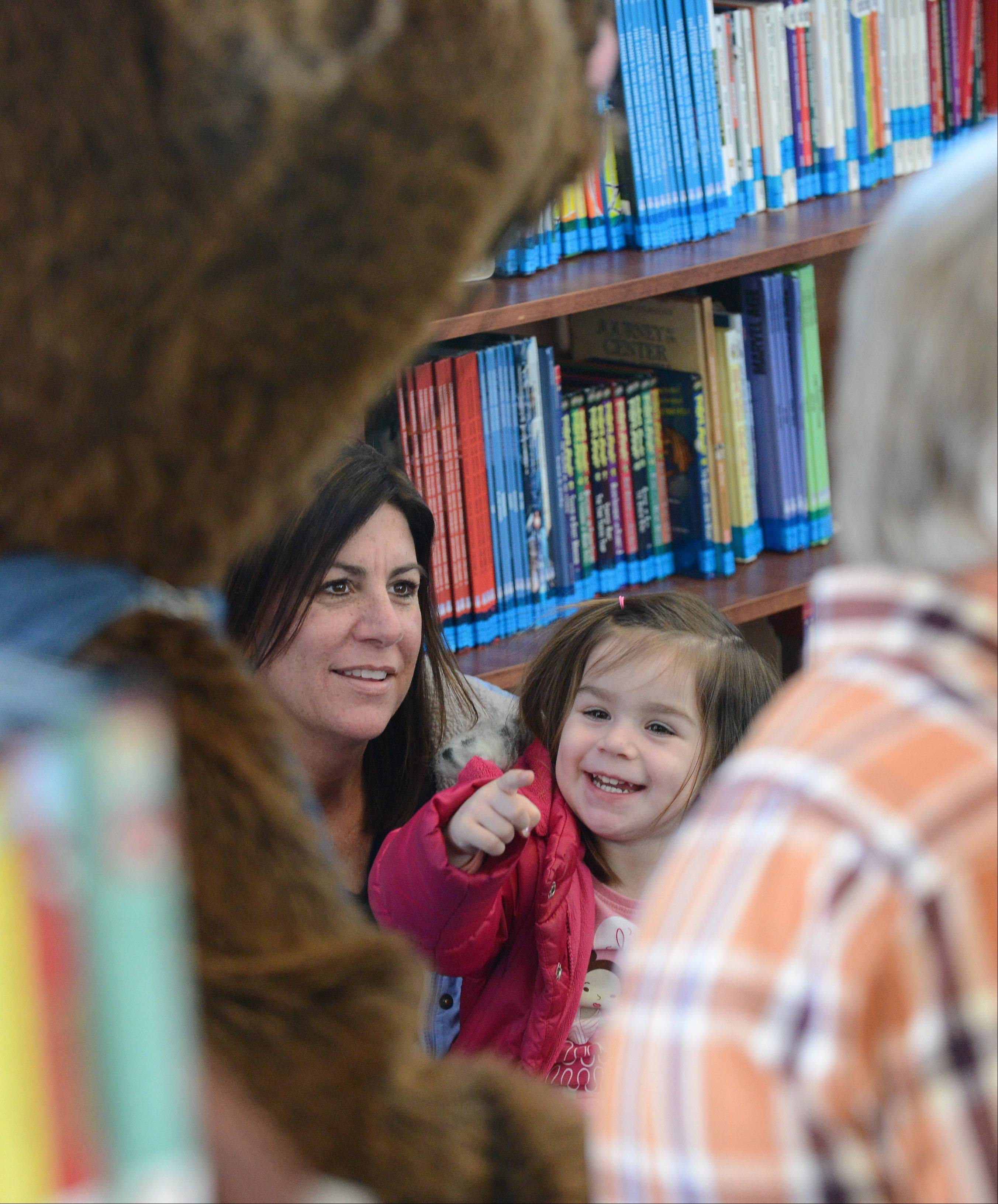 "Maryn Iwanski points at Cookie Mouse as she listens to the story, ""If You Give a Mouse a Cookie,"" by Laura Numeroff with her mom, Amy, Friday at the Town and Country Library in Elburn."