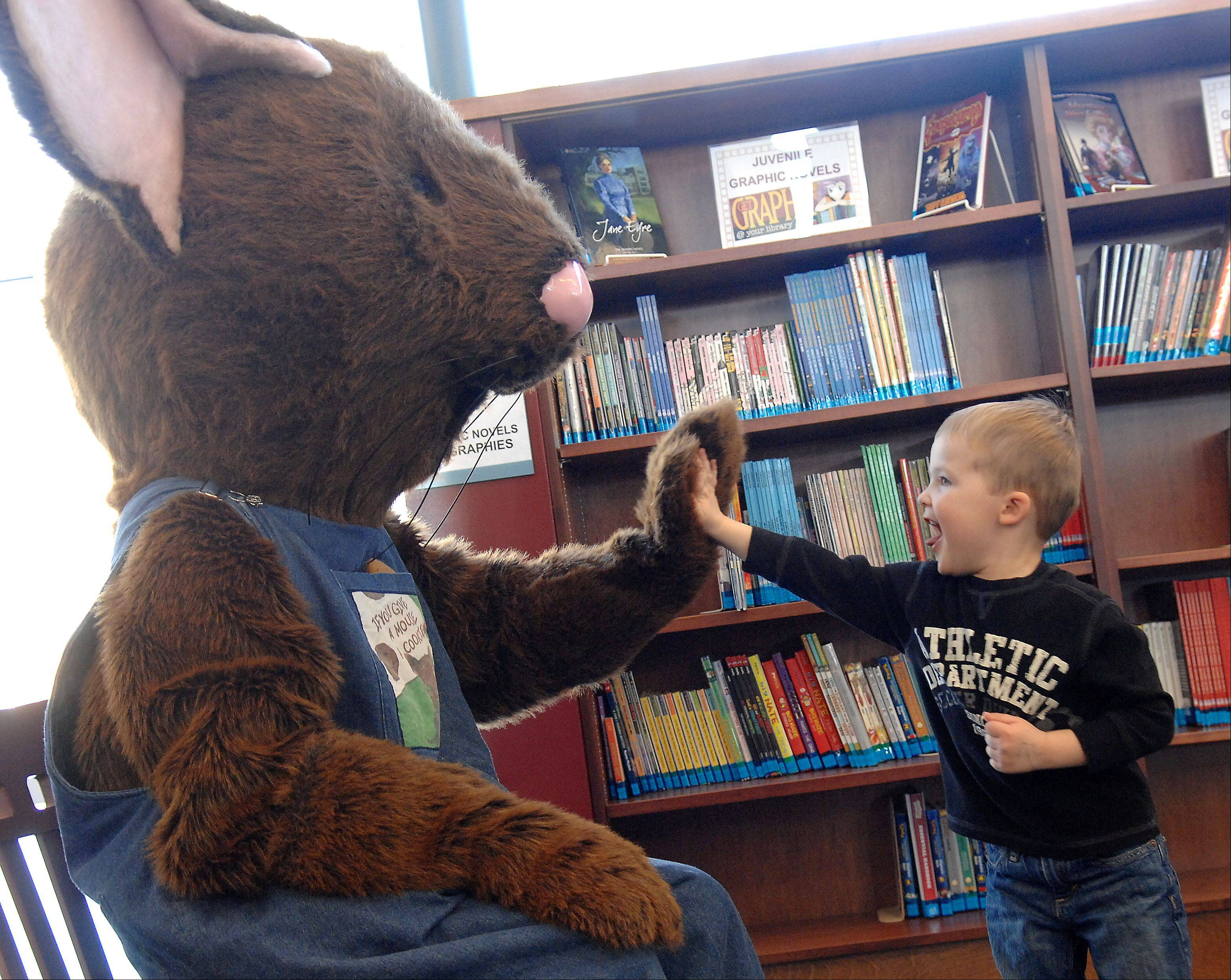 "Connor McCarty, 3, of Elburn gets a high-five from Cookie Mouse, star of the book, ""If You Give a Mouse a Cookie,"" Friday at the Town and Country Library in Elburn."