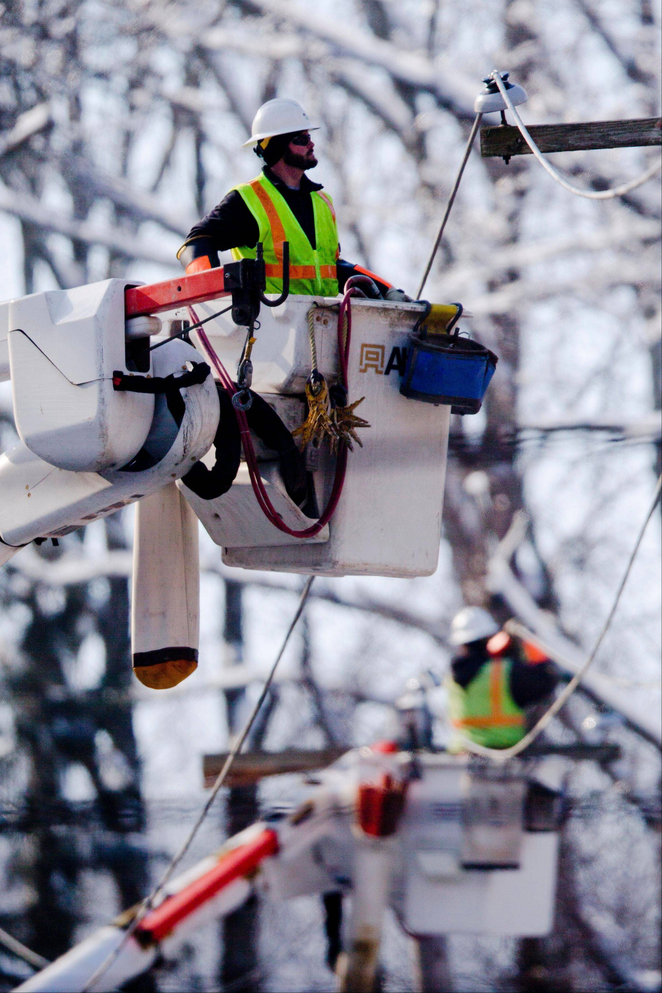 Linesman work to restore electrical power Friday in Downingtown, Pa.