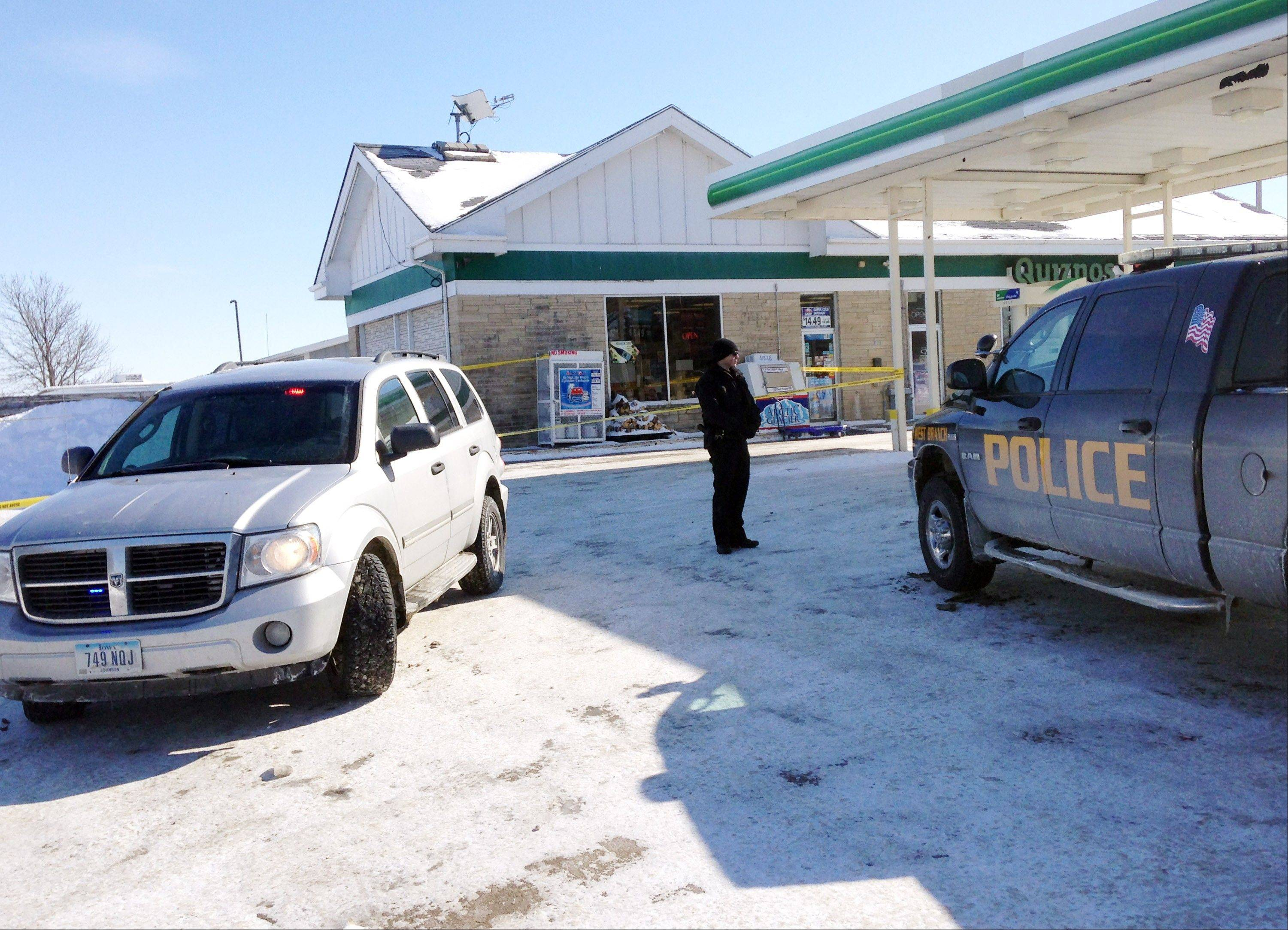 Authorities gather at a gas station in West Branch, Iowa, where a missing newborn was found alive Friday.