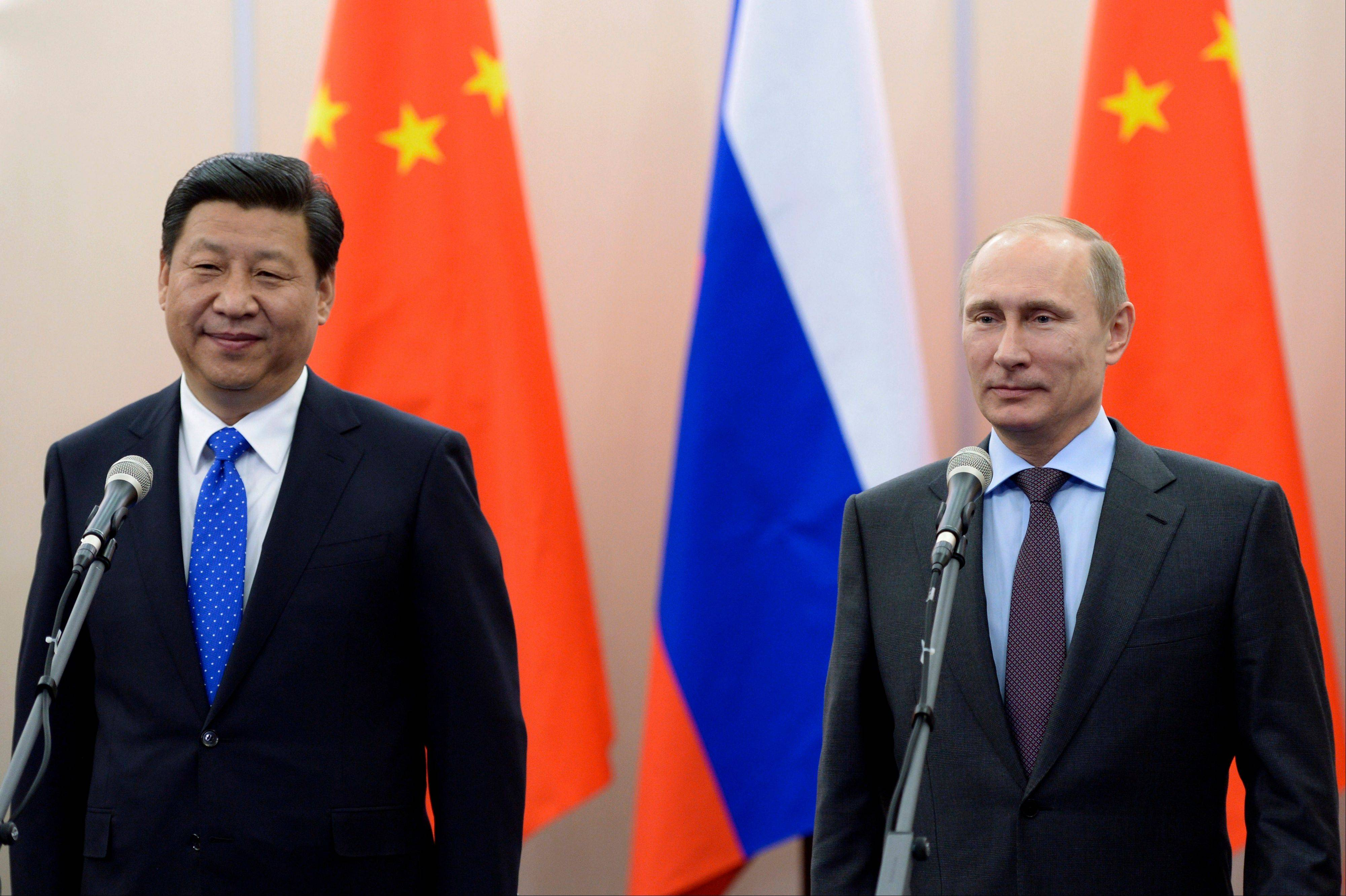 Russian President Vladimir Putin, right, and Chinese President Xi Jinping. Japanese Prime Minister Shinzo Abe and his Chinese counterpart Xi -- the leaders of the world's second and third largest economies -- are going to Sochi.