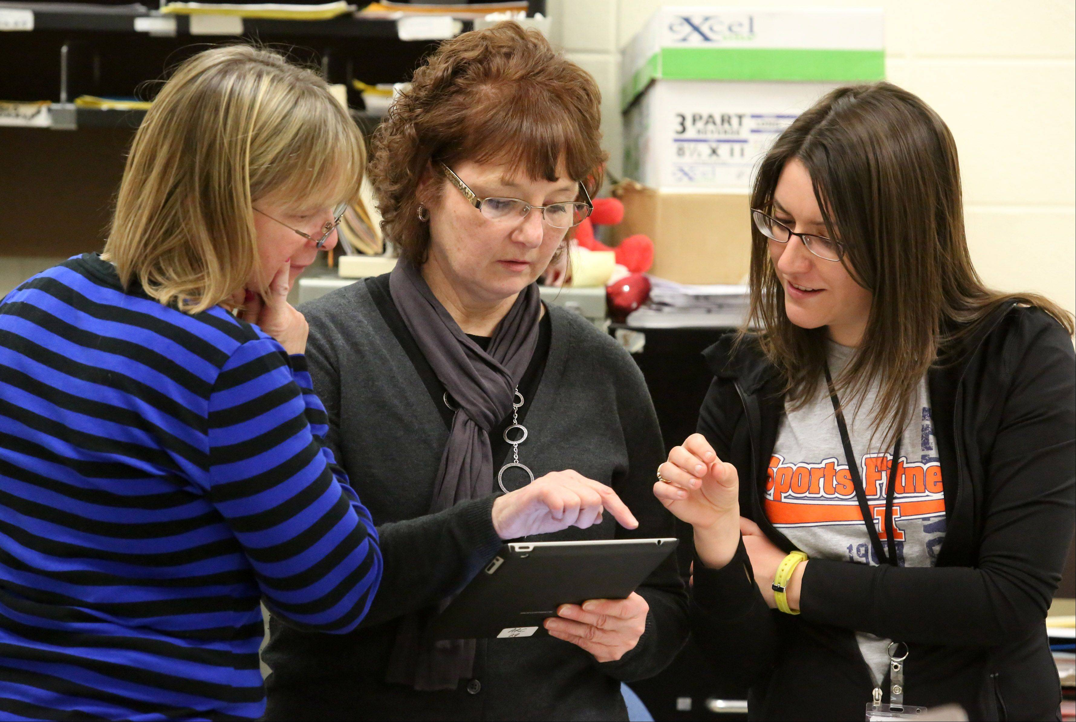 Hersey High School head librarian Katie Alexander, center, discusses how students access their District 214 accounts to complete their homework assignments in a health class with health teacher Sharon Meintzer, left, and student teacher Sarah Rodriguez.